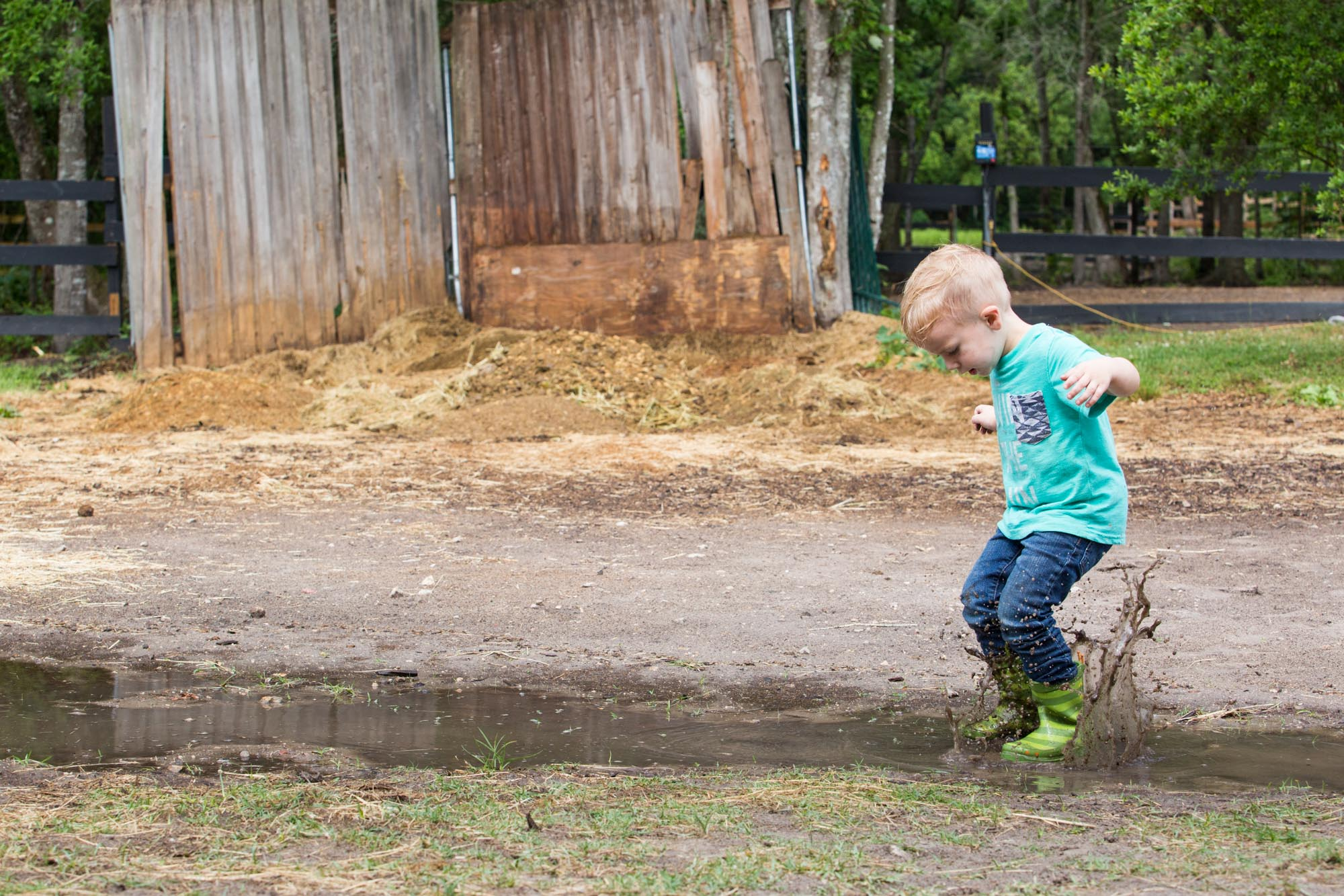 boy jumping in mud puddle