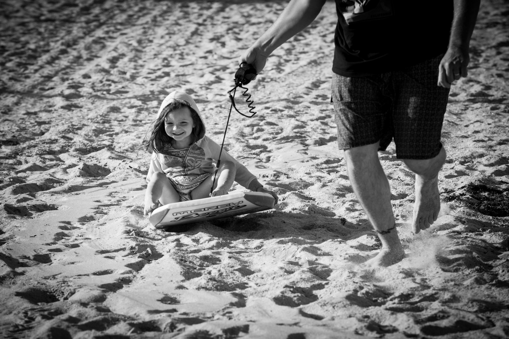 family sand surfing at beach