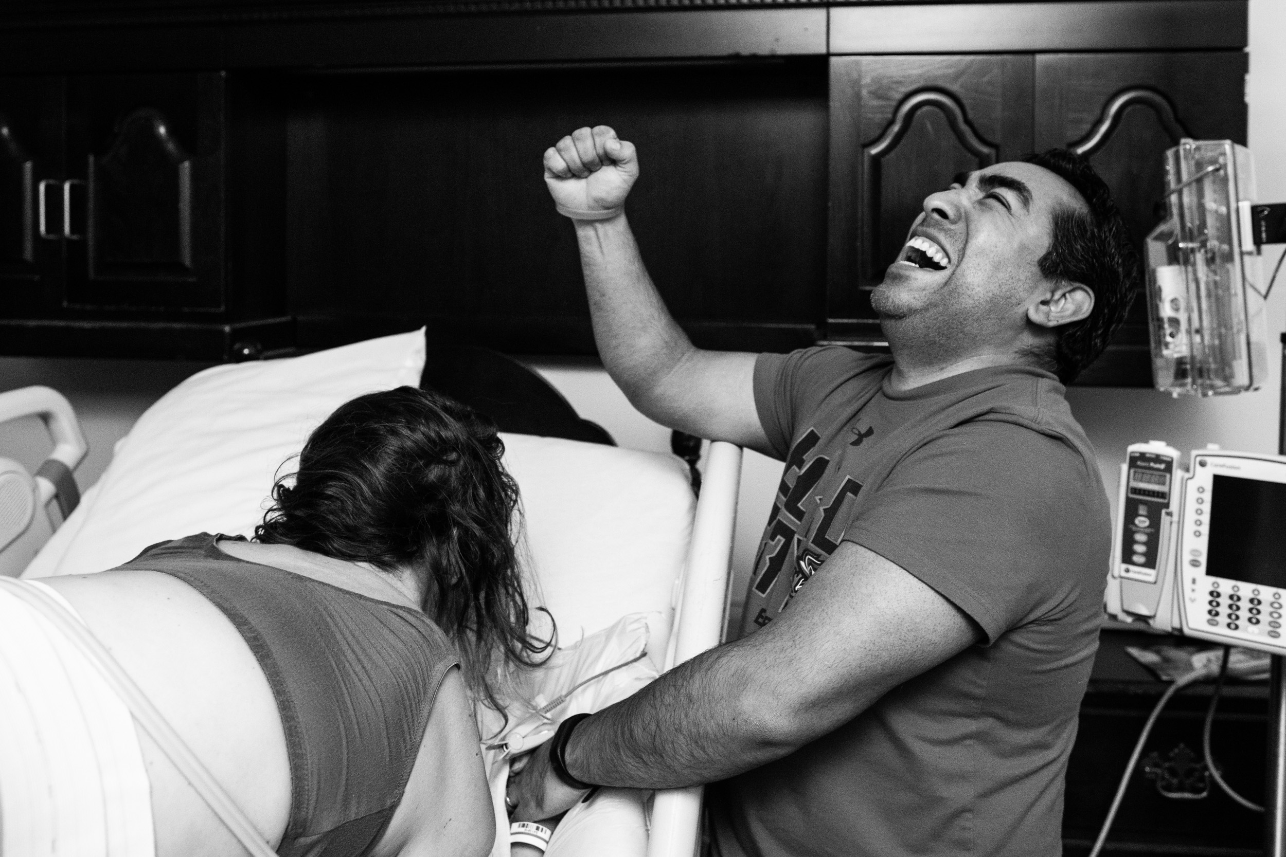 excited dad puts arm up to celebrate having a baby boy