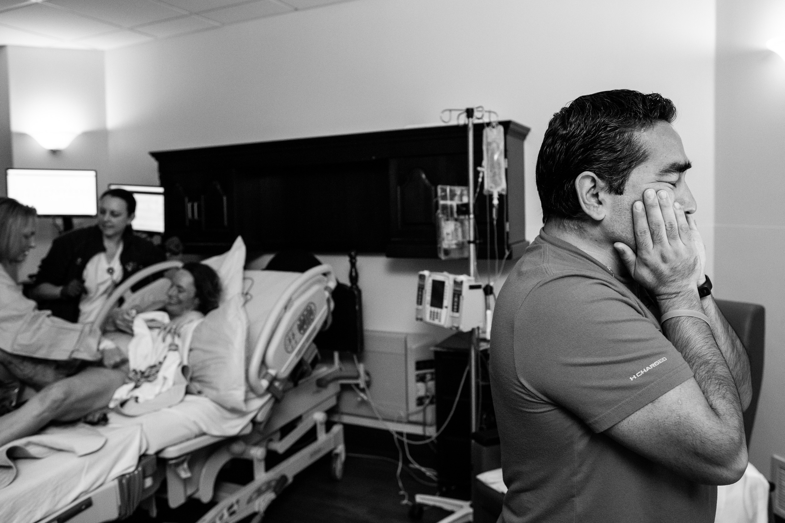 dad overcome with emotion after birth puts his hands on his face