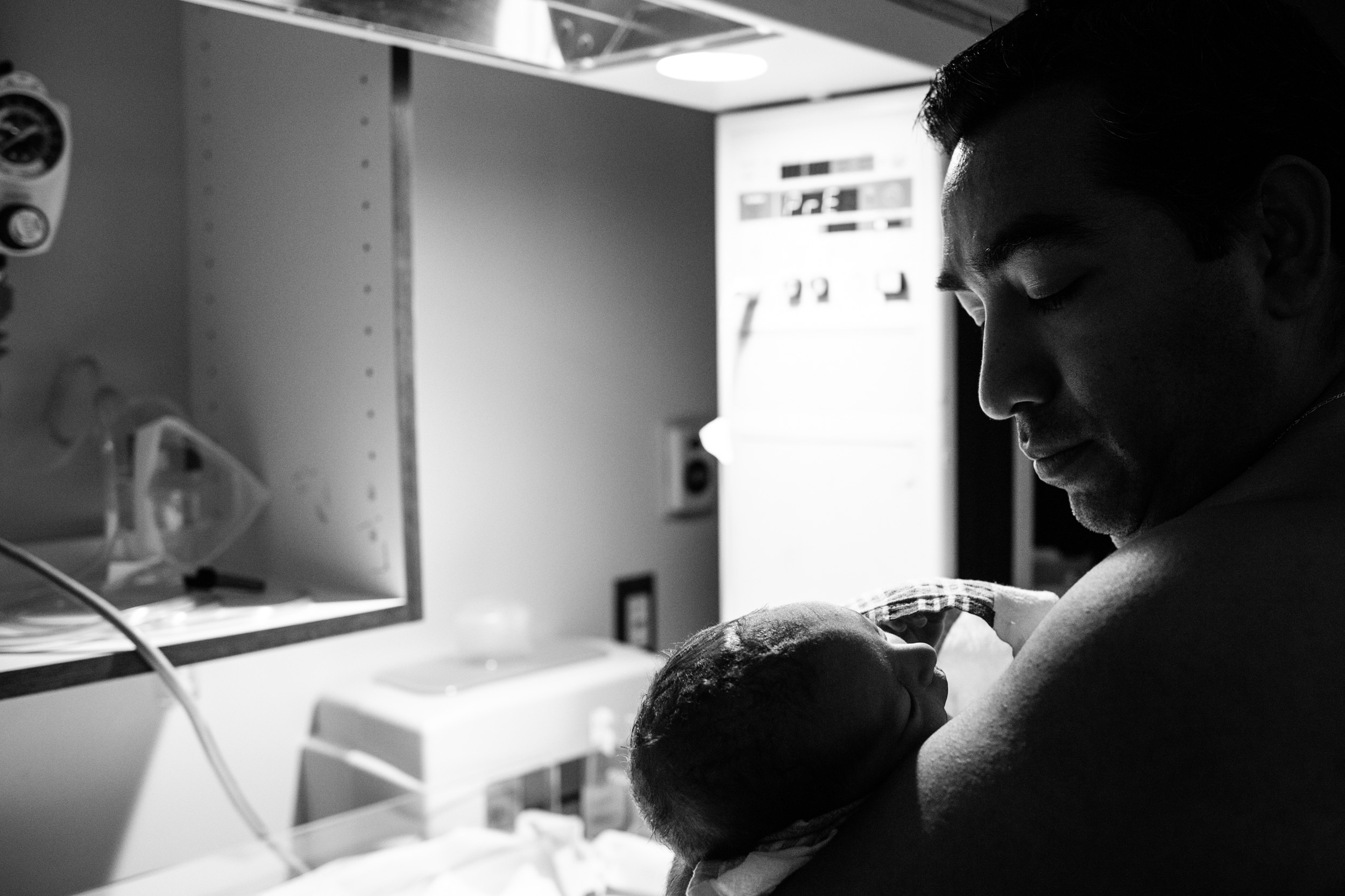 silhouette of dad looking at newborn baby