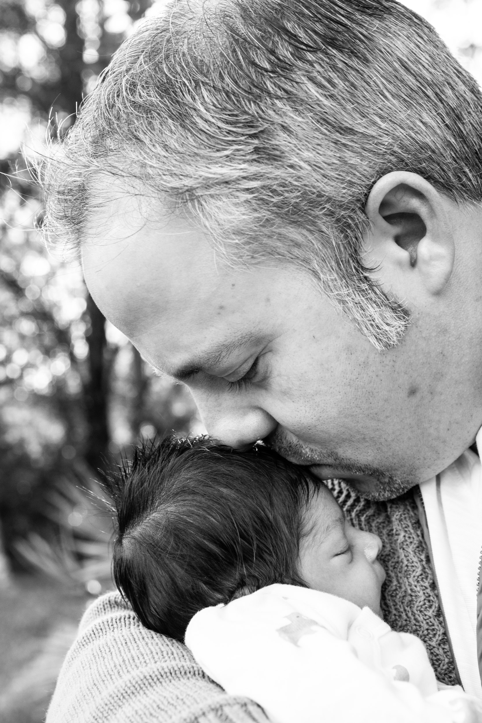 dad kissing newborn baby boy
