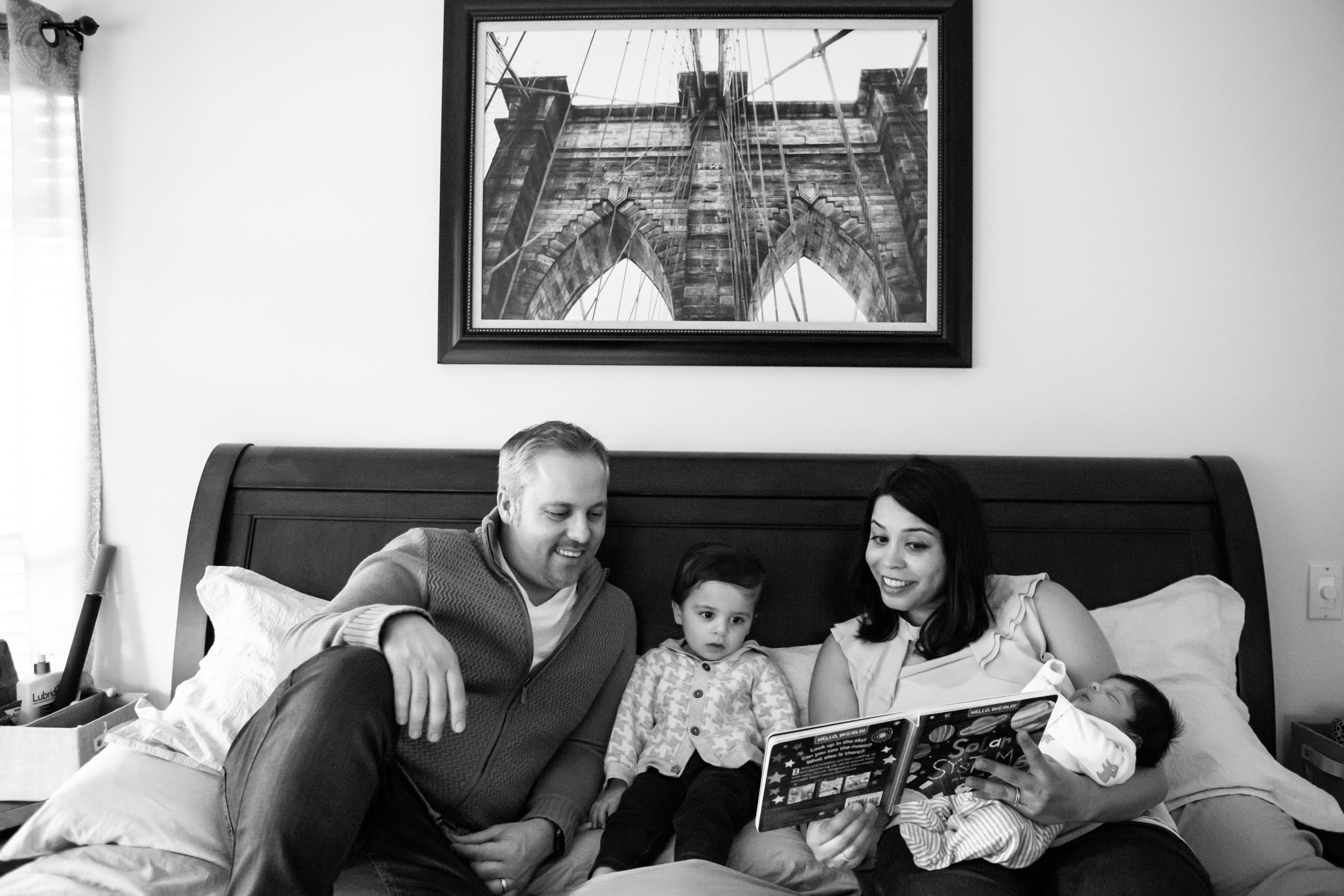 family with two small children reading a book