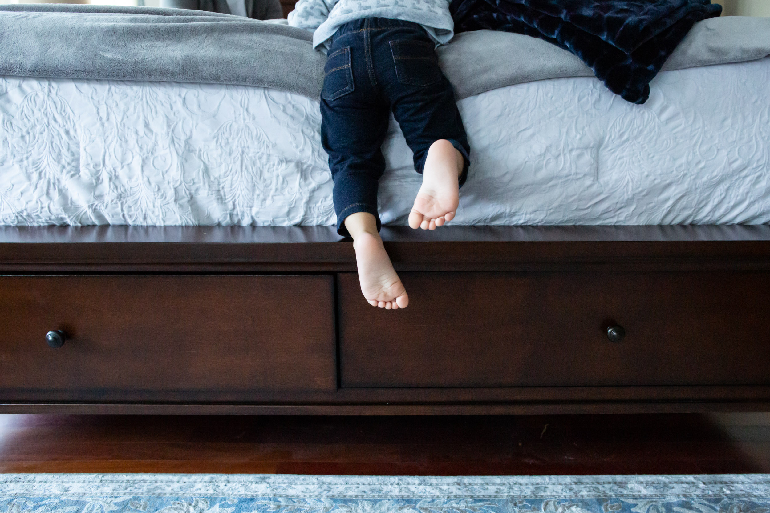 little boy's feet on edge of bed