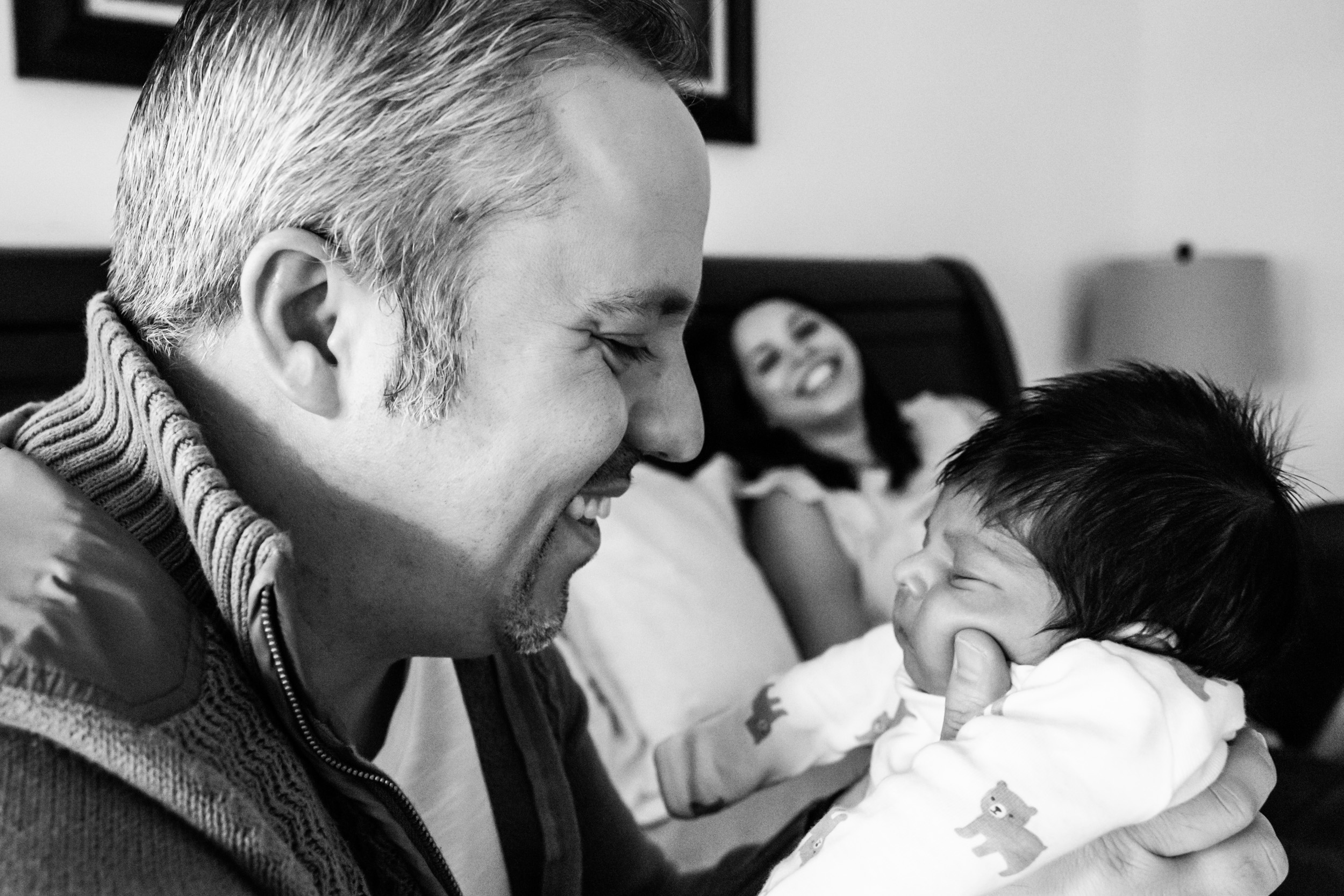 jacksonville dad holding and smiling at his newborn
