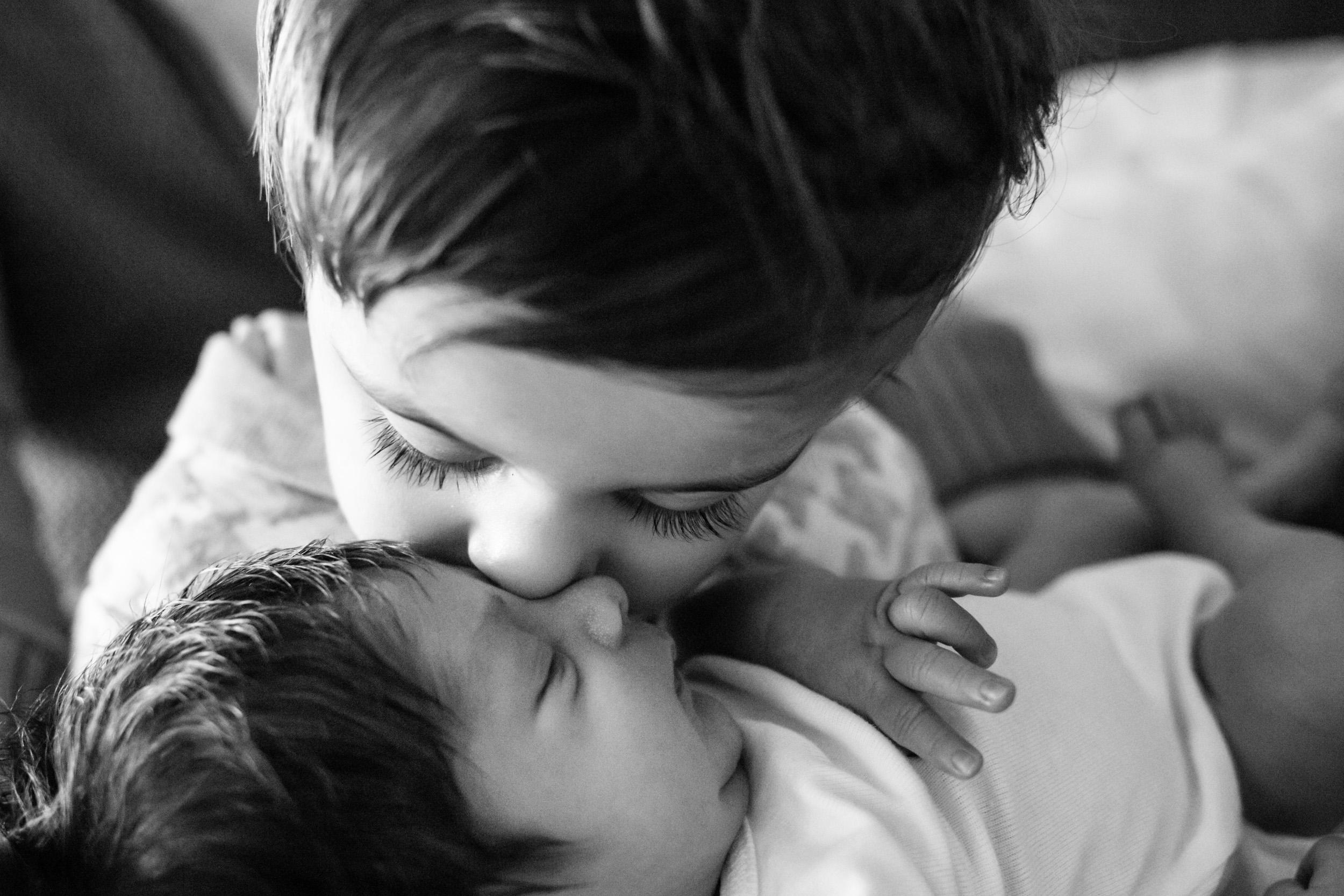 older brother kissing newborn baby boy