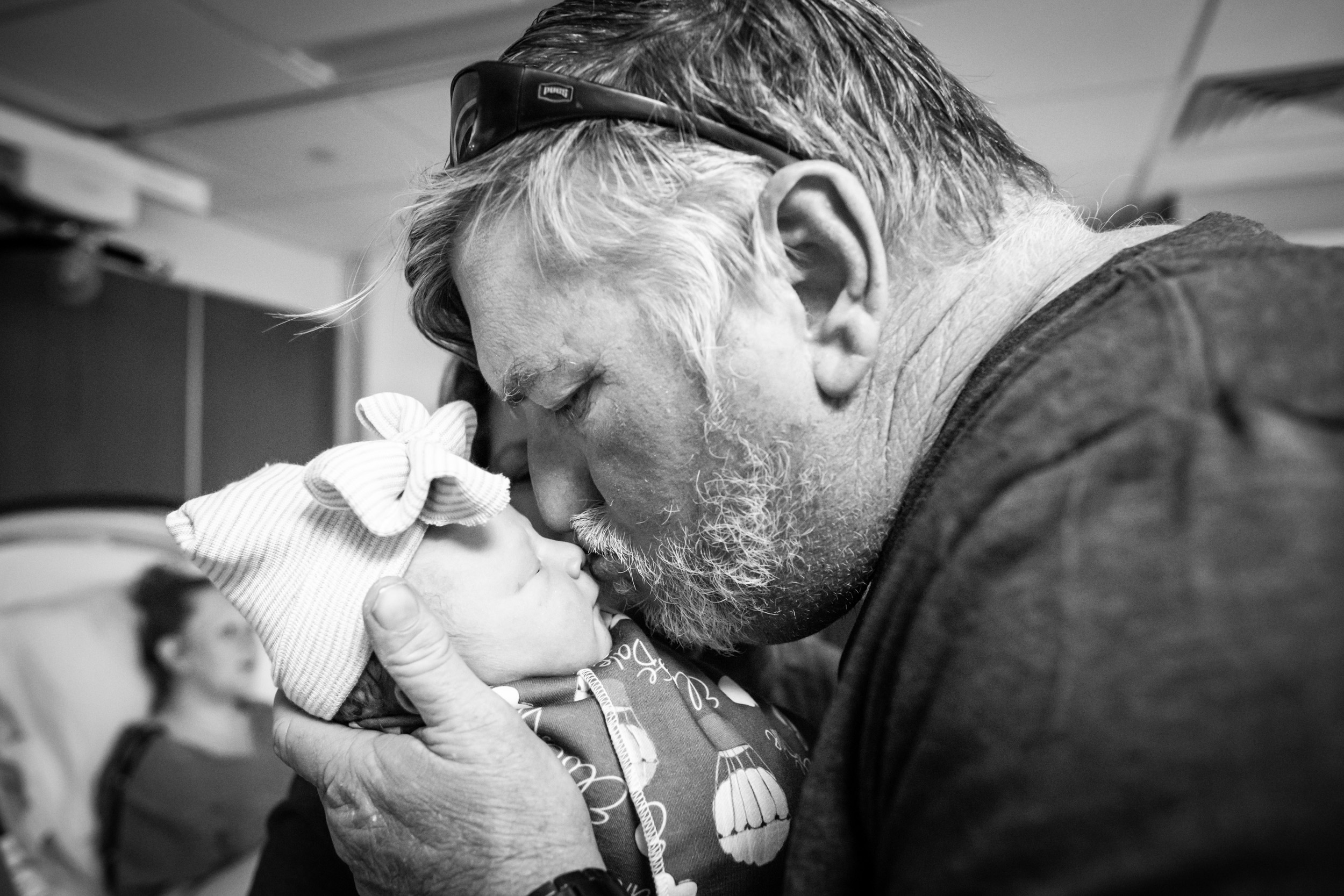 grandfather kissing his newborn granddaughter