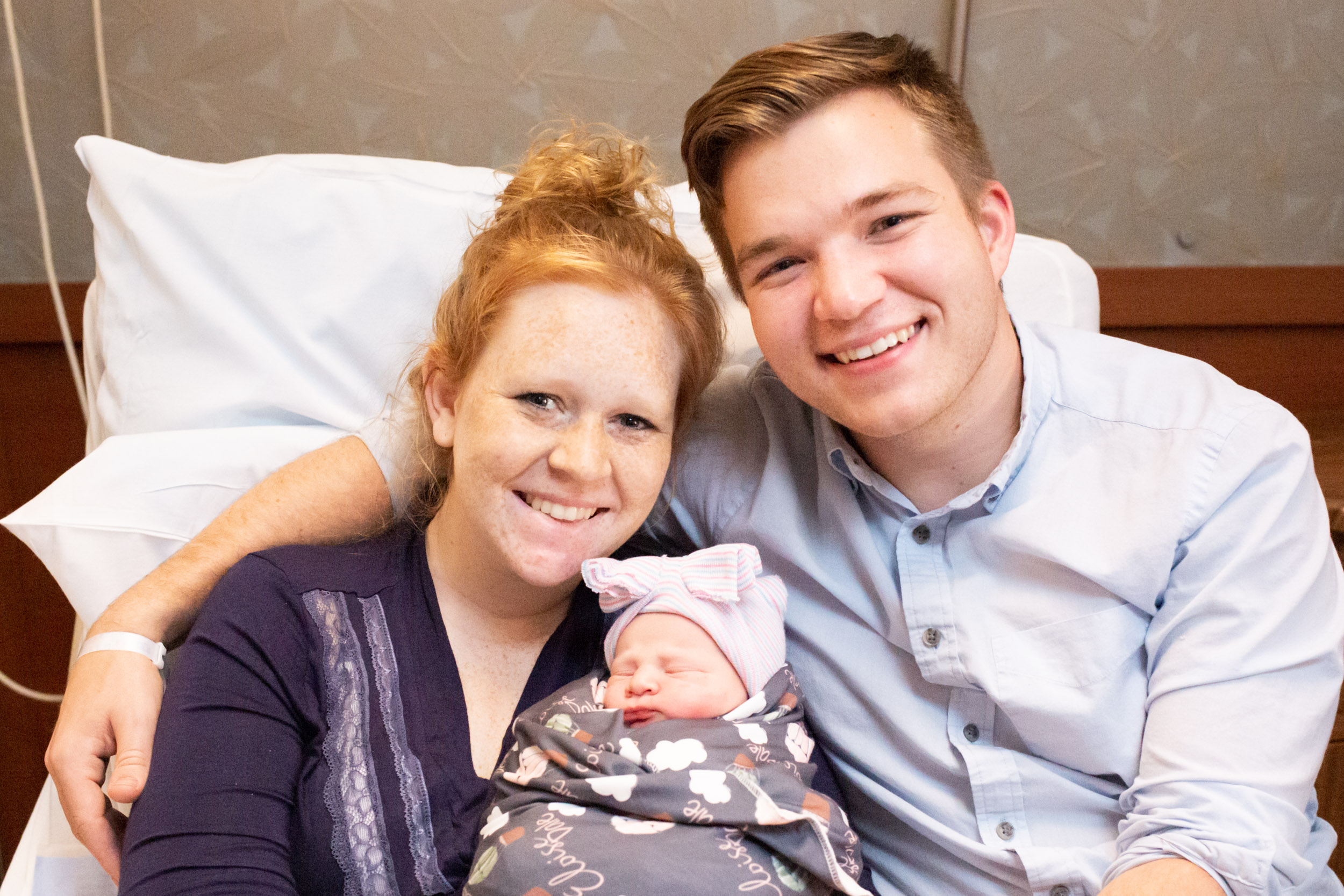 new parents smiling with newborn