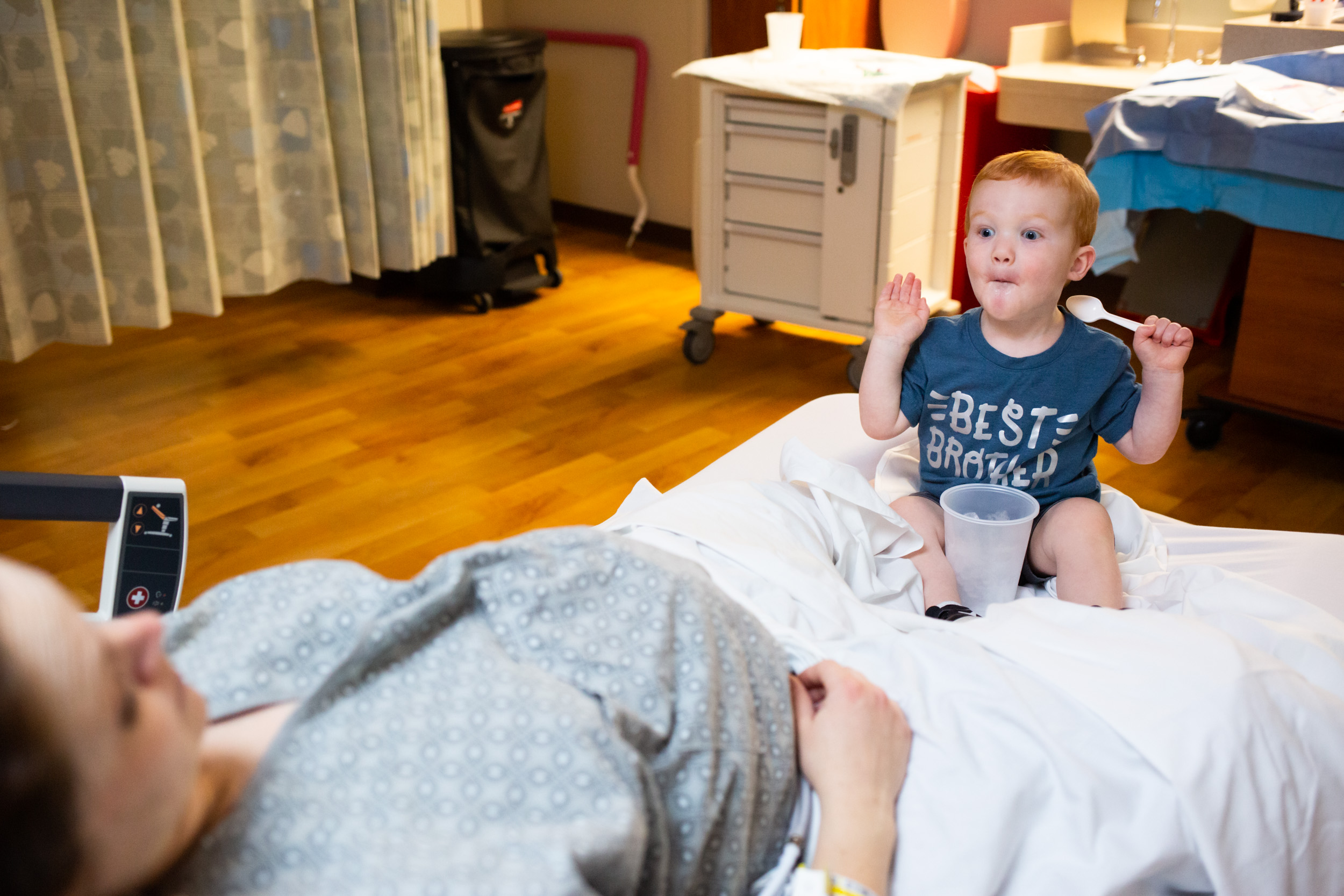 little boy making his mom laugh in hospital room during her labor