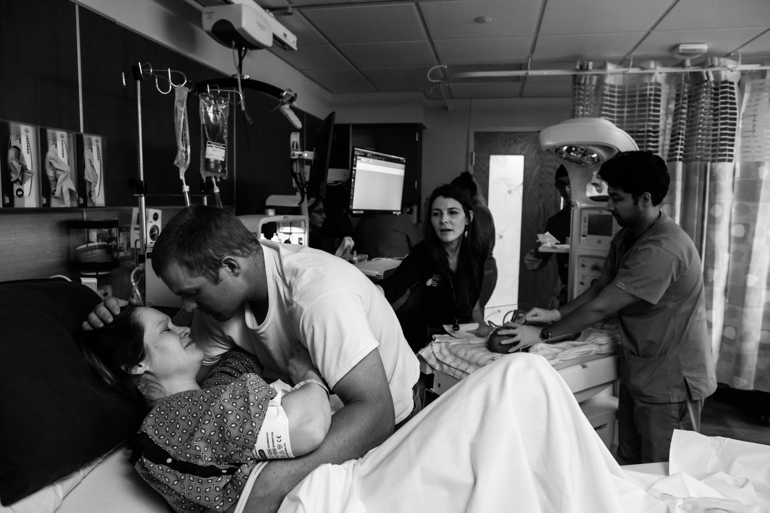 husband and wife comforting each other while baby being brought over so they could see him
