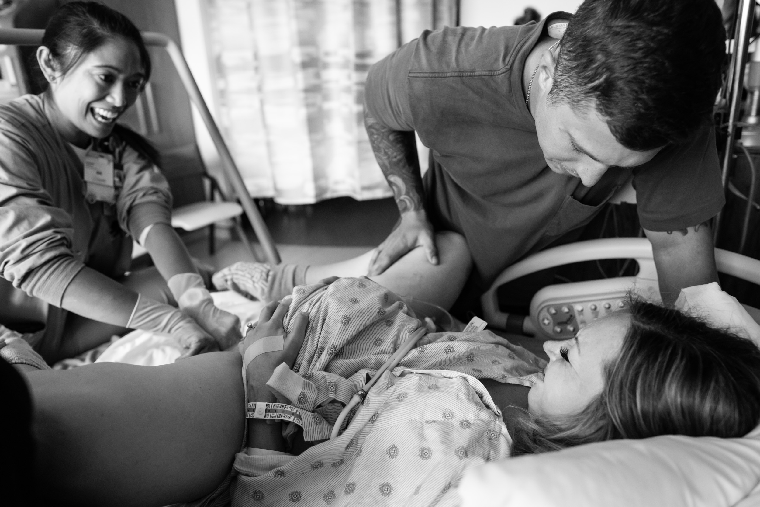 birth mom pushing during labor with her husband and nurse