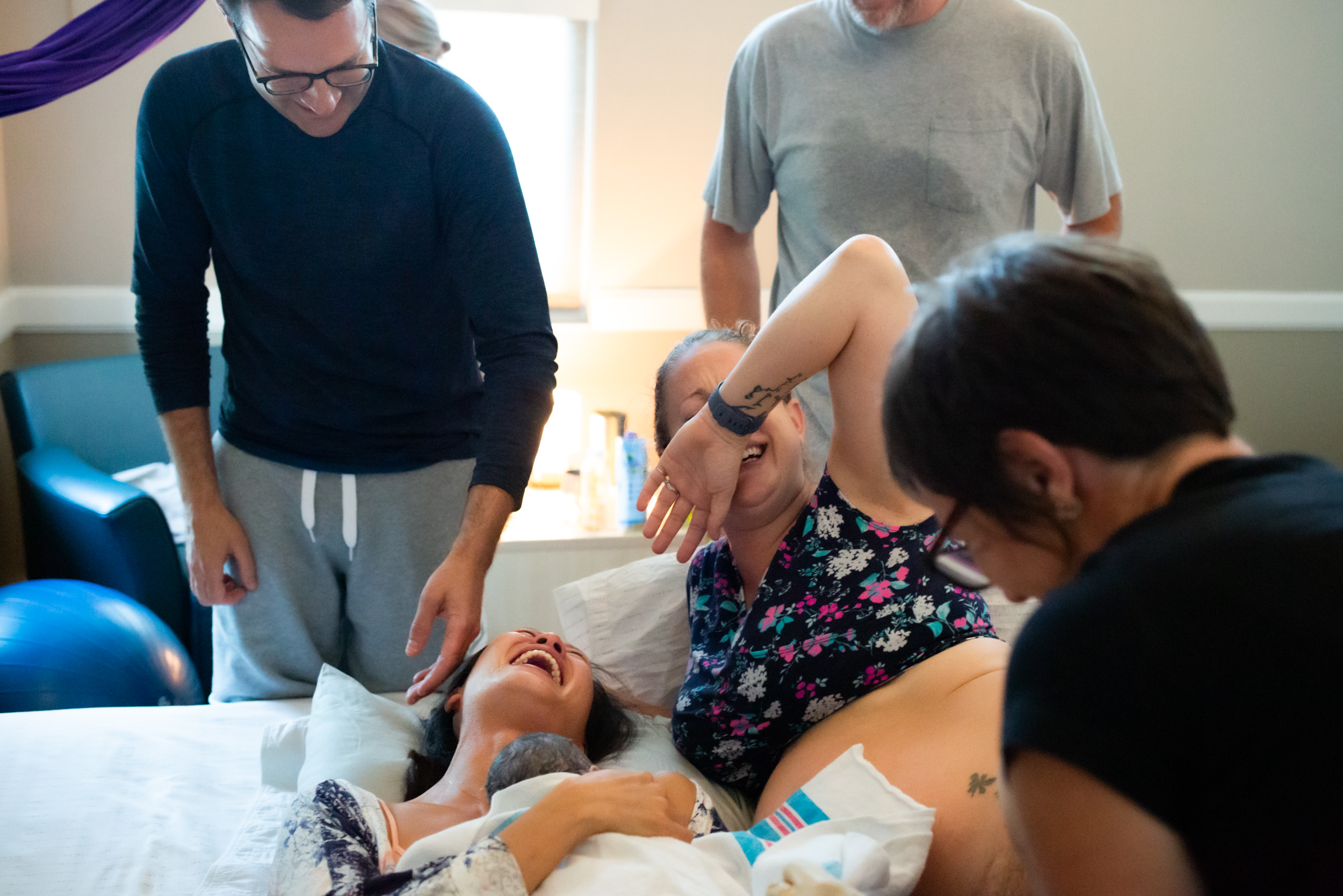 surrogate mom laughing with new parents after birth