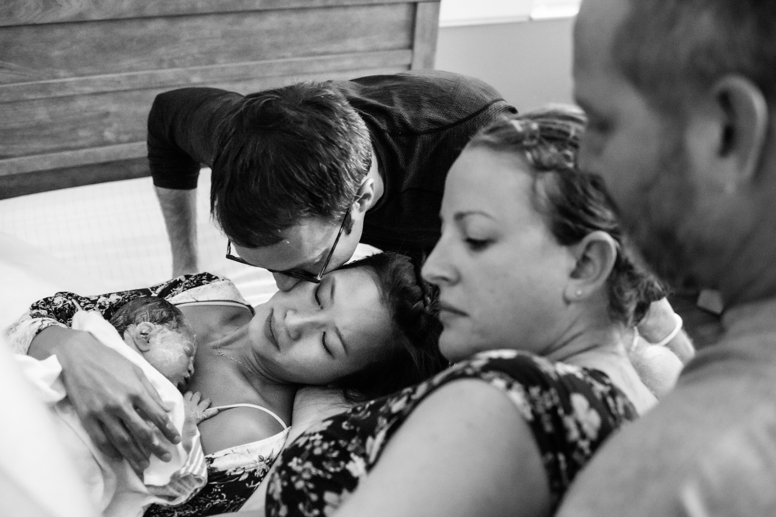 new dad kissing his wife after baby boy born through surrogacy