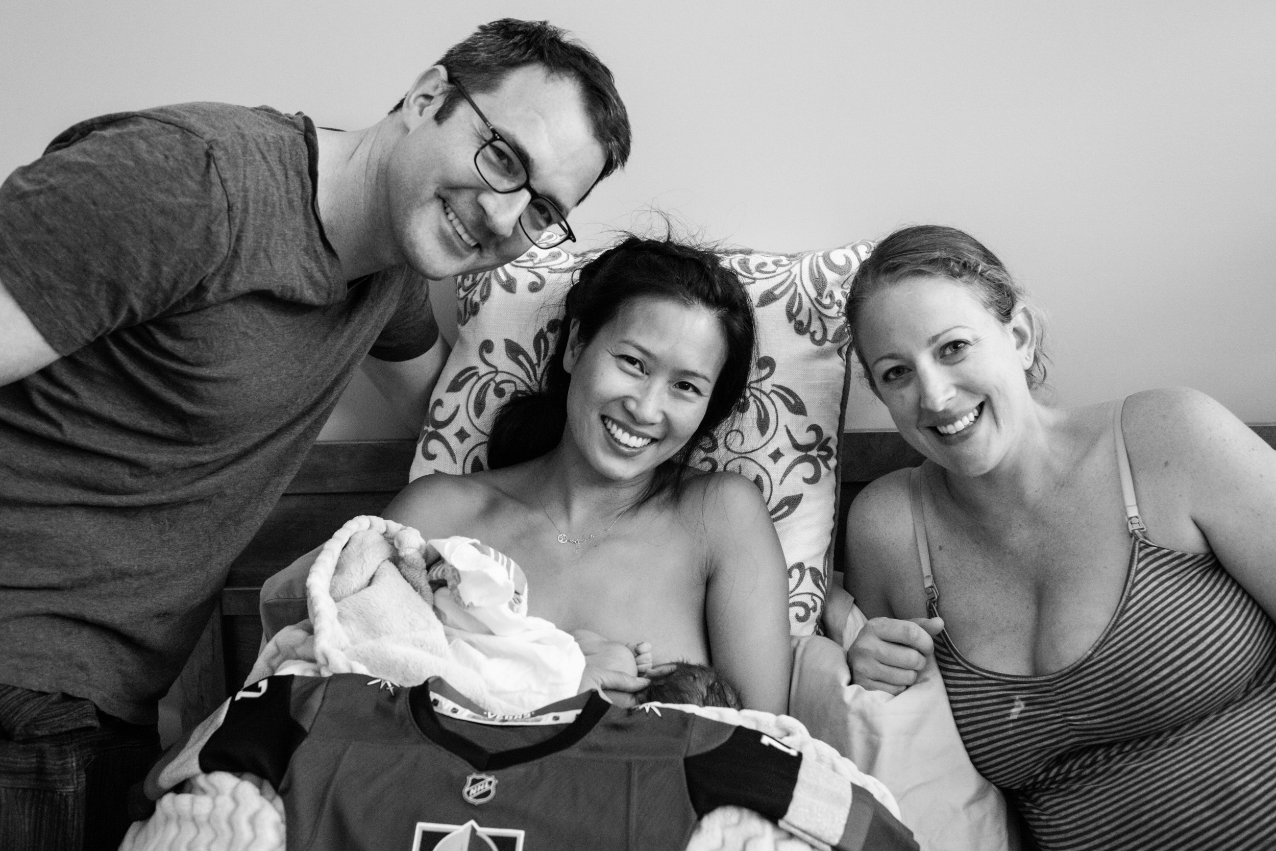 group portrait of new parents and surrogate mother with newborn baby boy