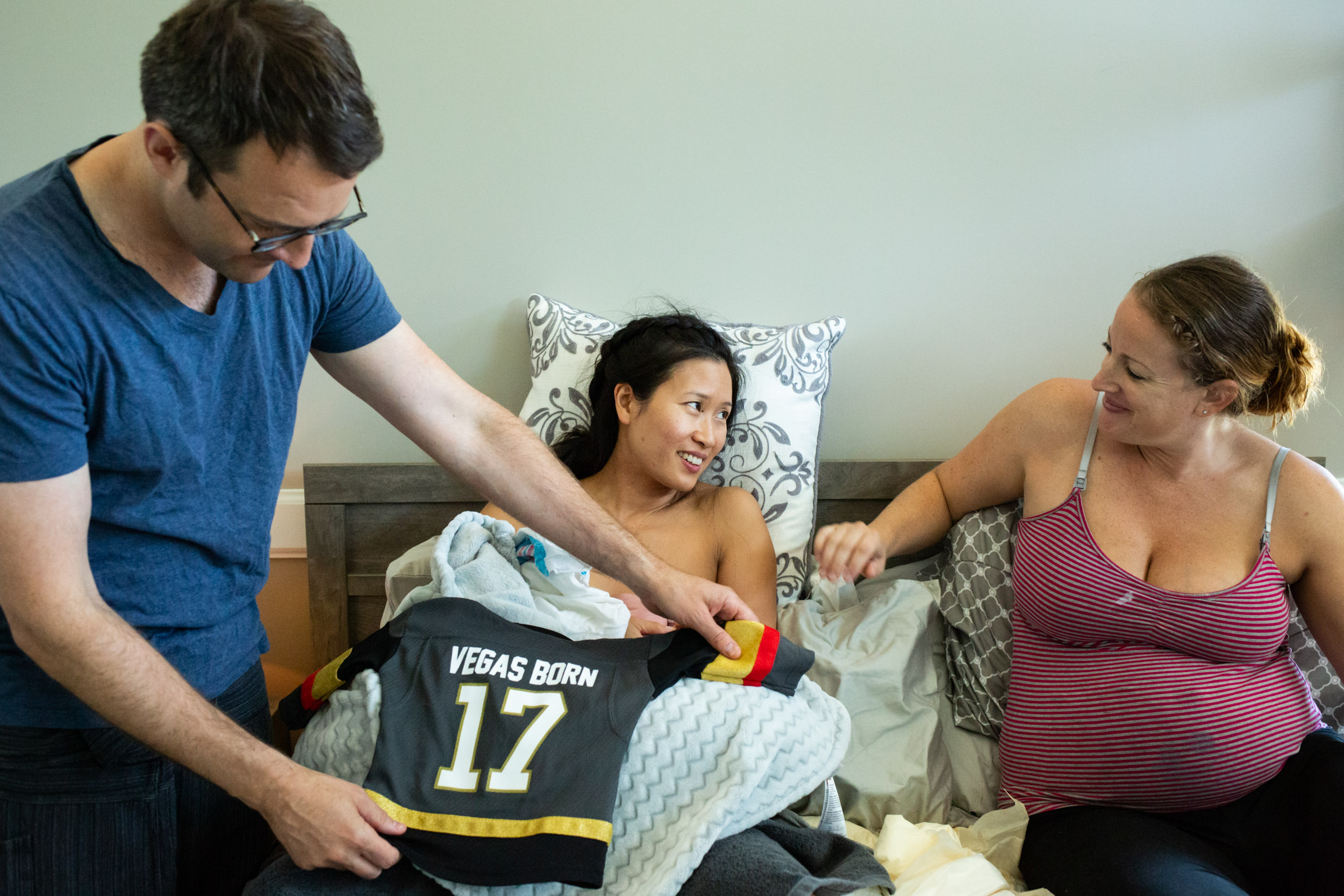 new parents with newborn baby and surrogate mom smiling at each other