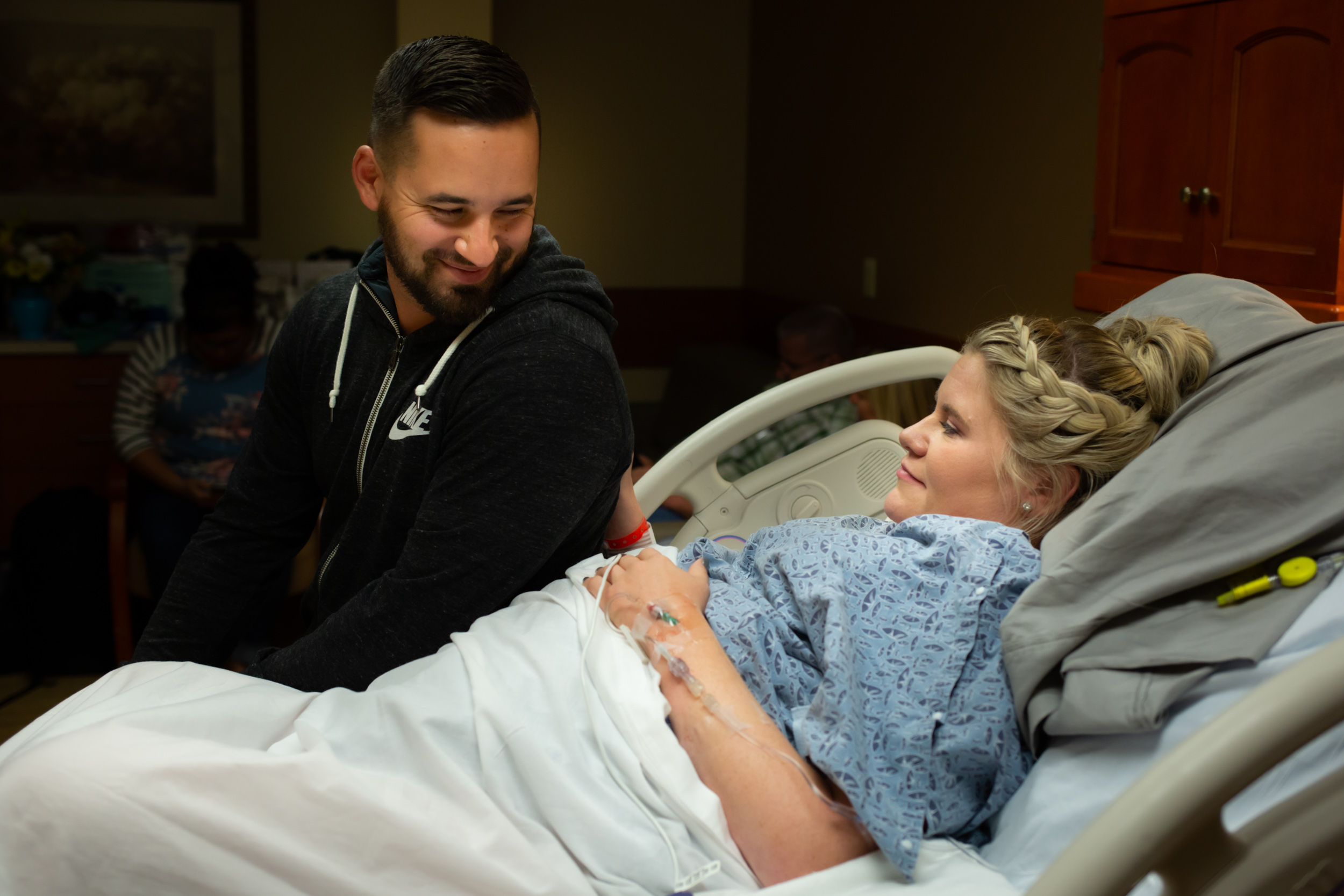 jacksonville husband and wife sitting on hospital bed smiling waiting for birth