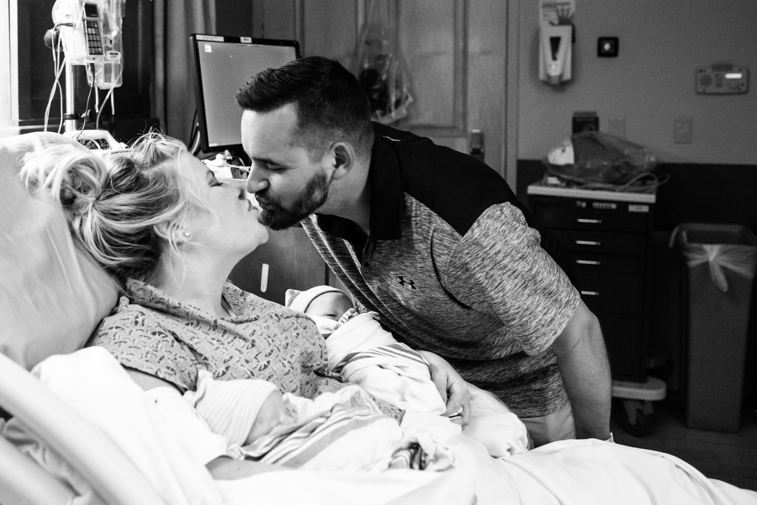 new parents kissing after birth