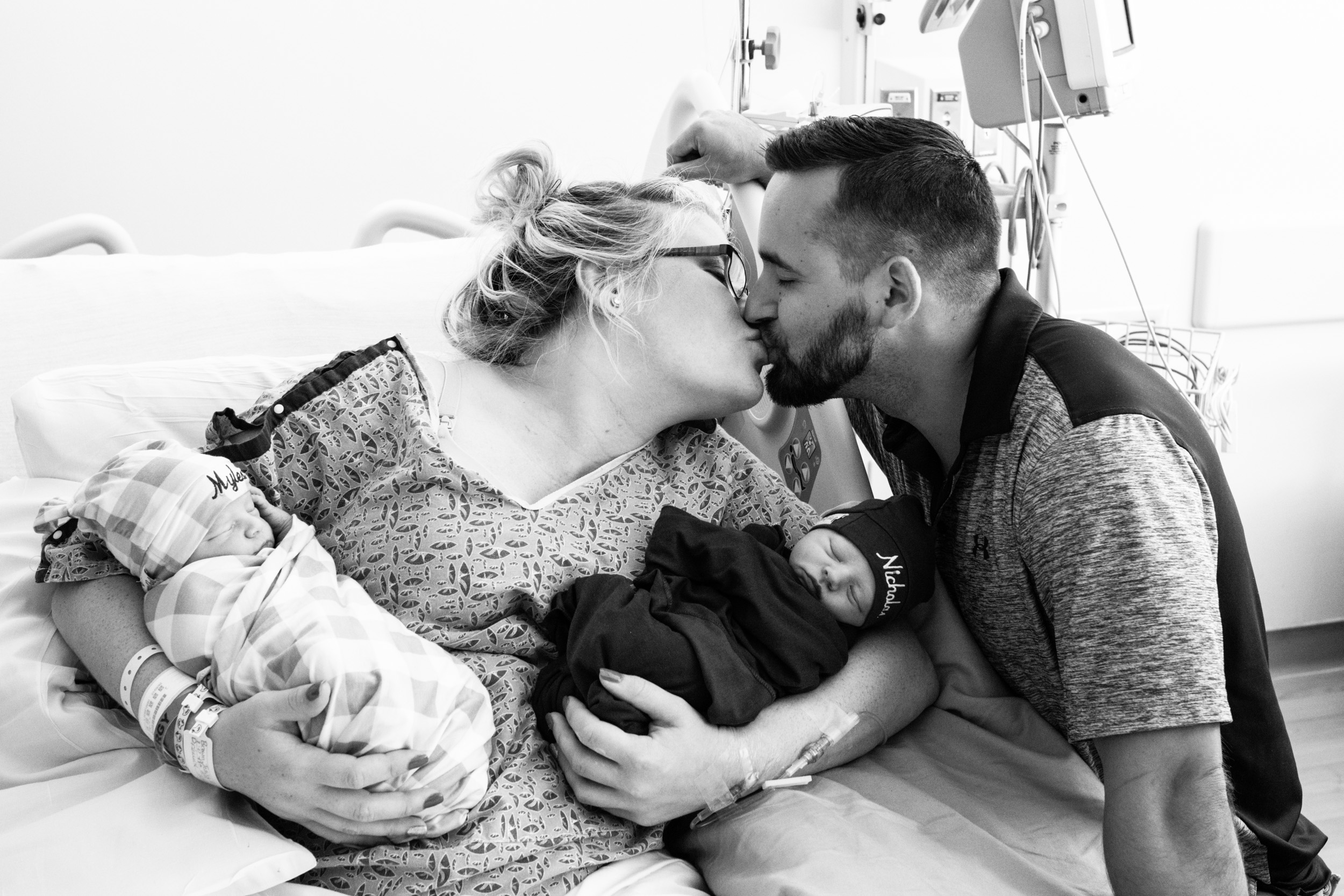 jacksonville twin parents kissing while holding newborn babies