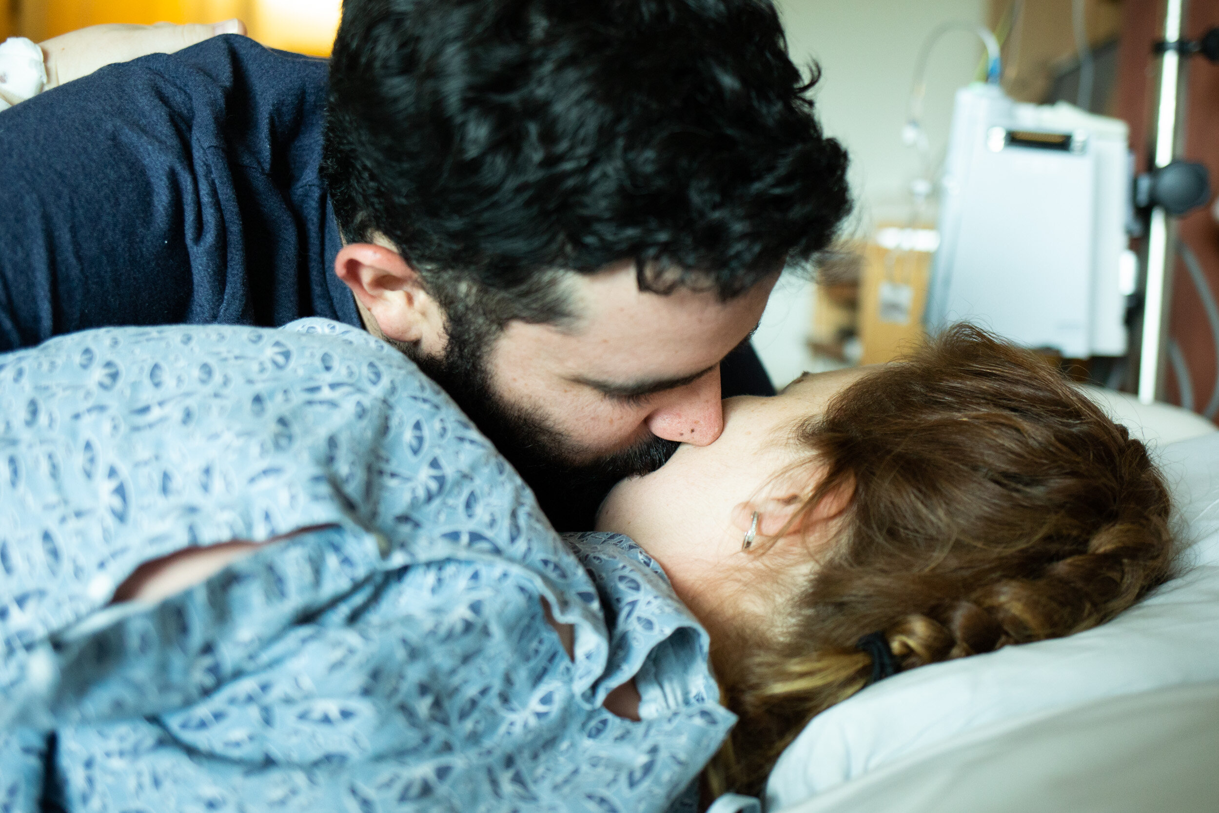 husband kissing wife before birth of their baby