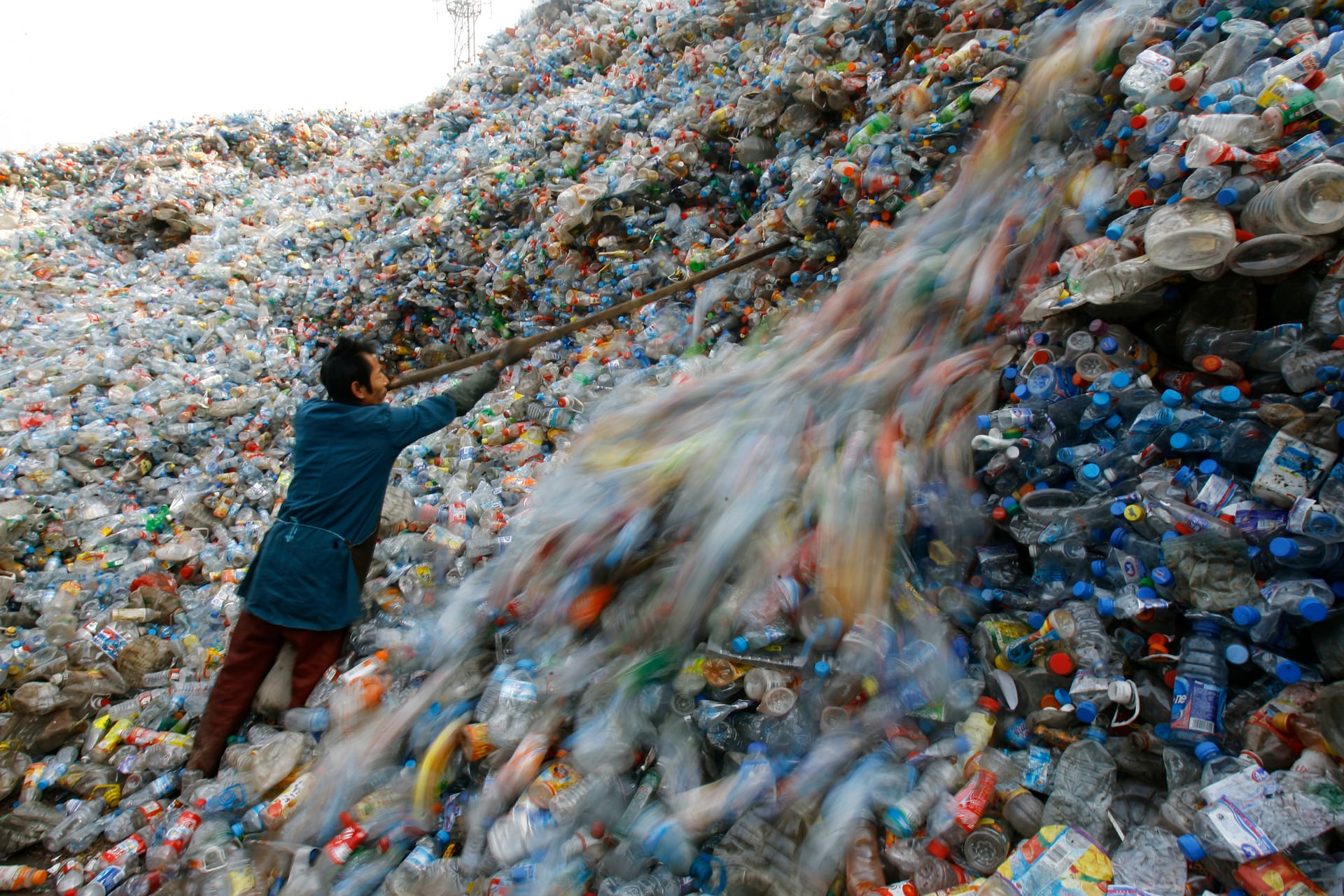 A worker sorts out plastic waste / Source: The Guardian