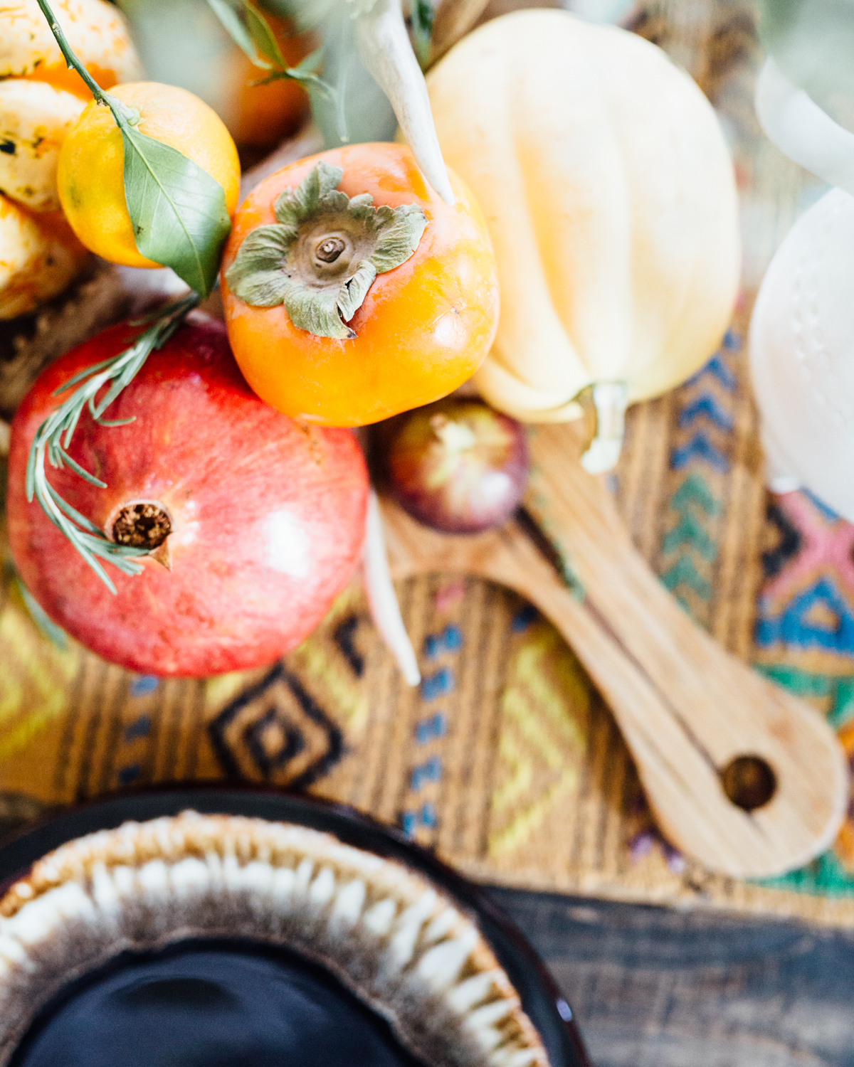 Seasonal farmers market goodness like squash, persimmon, and pomegranate create a charming and inexpensive harvested centerpiece.