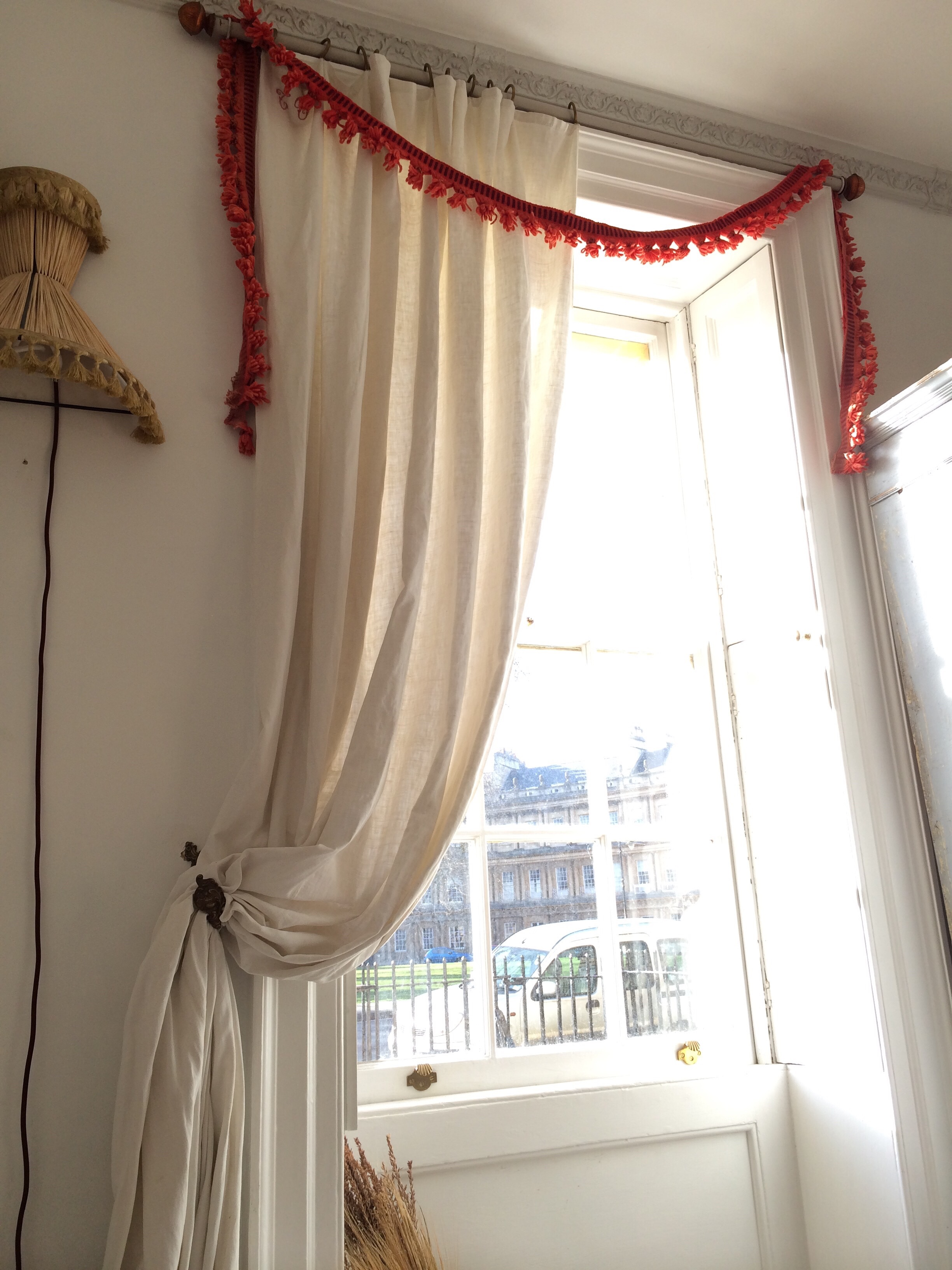 Felicity masters the high + low appeal.A garland of antique trimmings hang from the ornate crown molding of the windowsill.