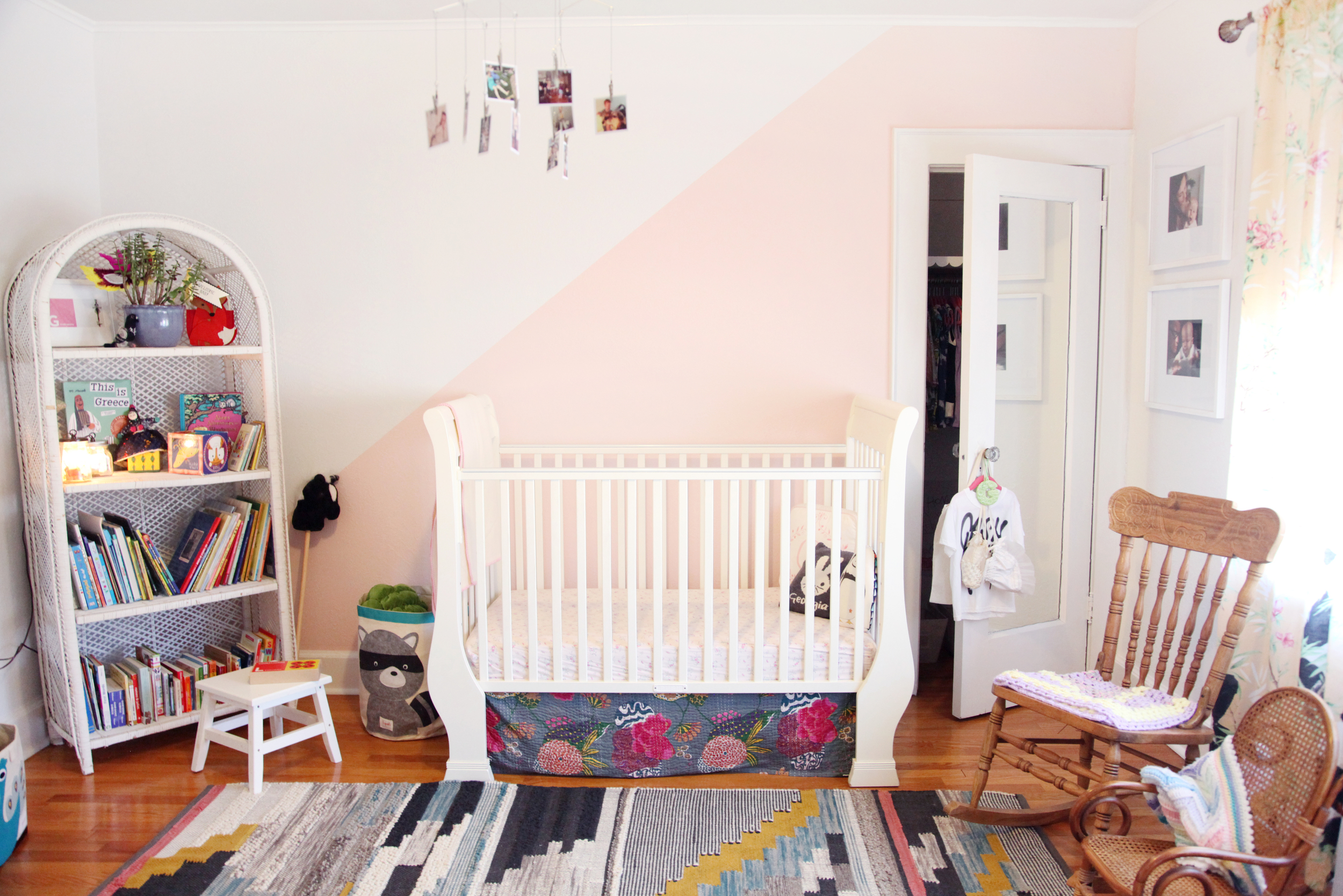 Wicker white bookshelf scored at a local church sale and a West Elm statement rug. Pale pink paint slices the wall.
