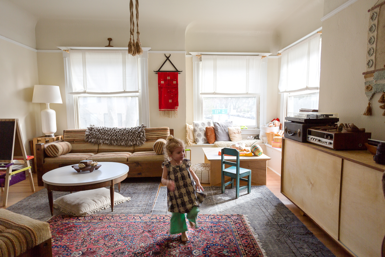 Craigslist couch scores and some dramatic fan tassels. Edie dances in her own little bohemian baby nook.