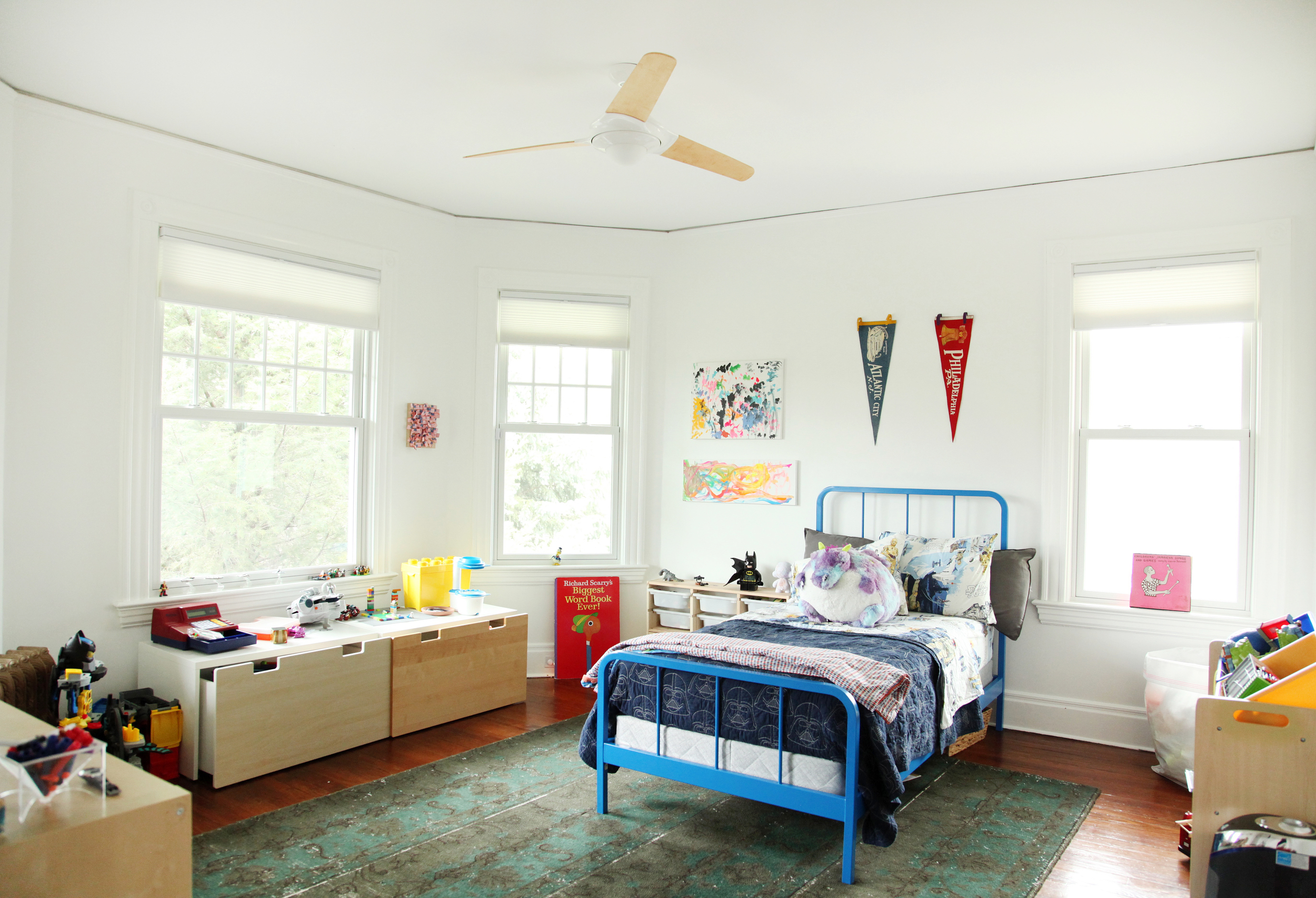 """Desmond's room- """" as tidy as a five year old boy's room can b e""""-old pennants that used to hang in Thomas' office along with Desmond's own art hang on the walls. Bed is   Land of Nod ."""