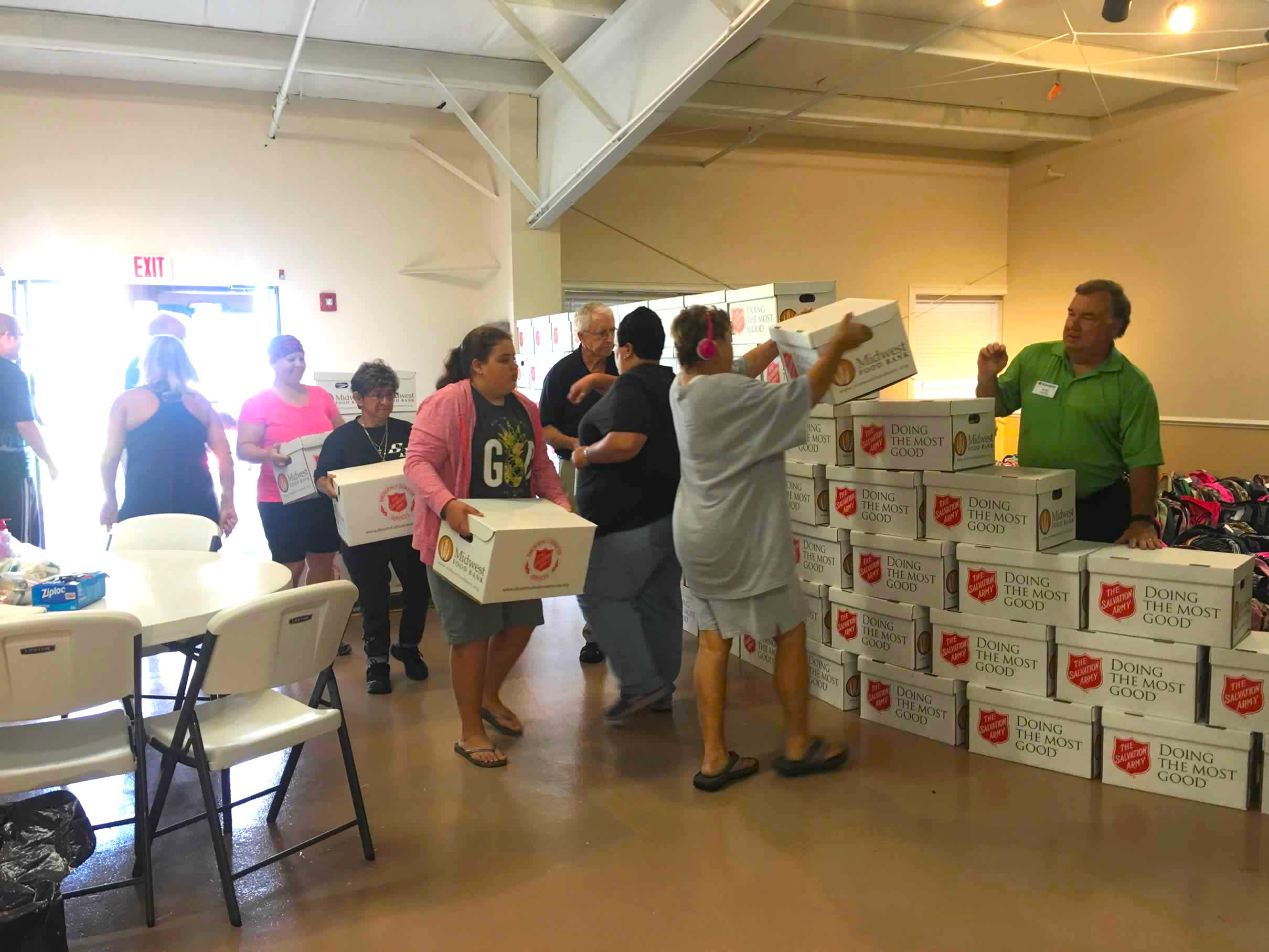 Volunteers create wall of food donations from the Salvation Army, one of the Kiwanis partners.