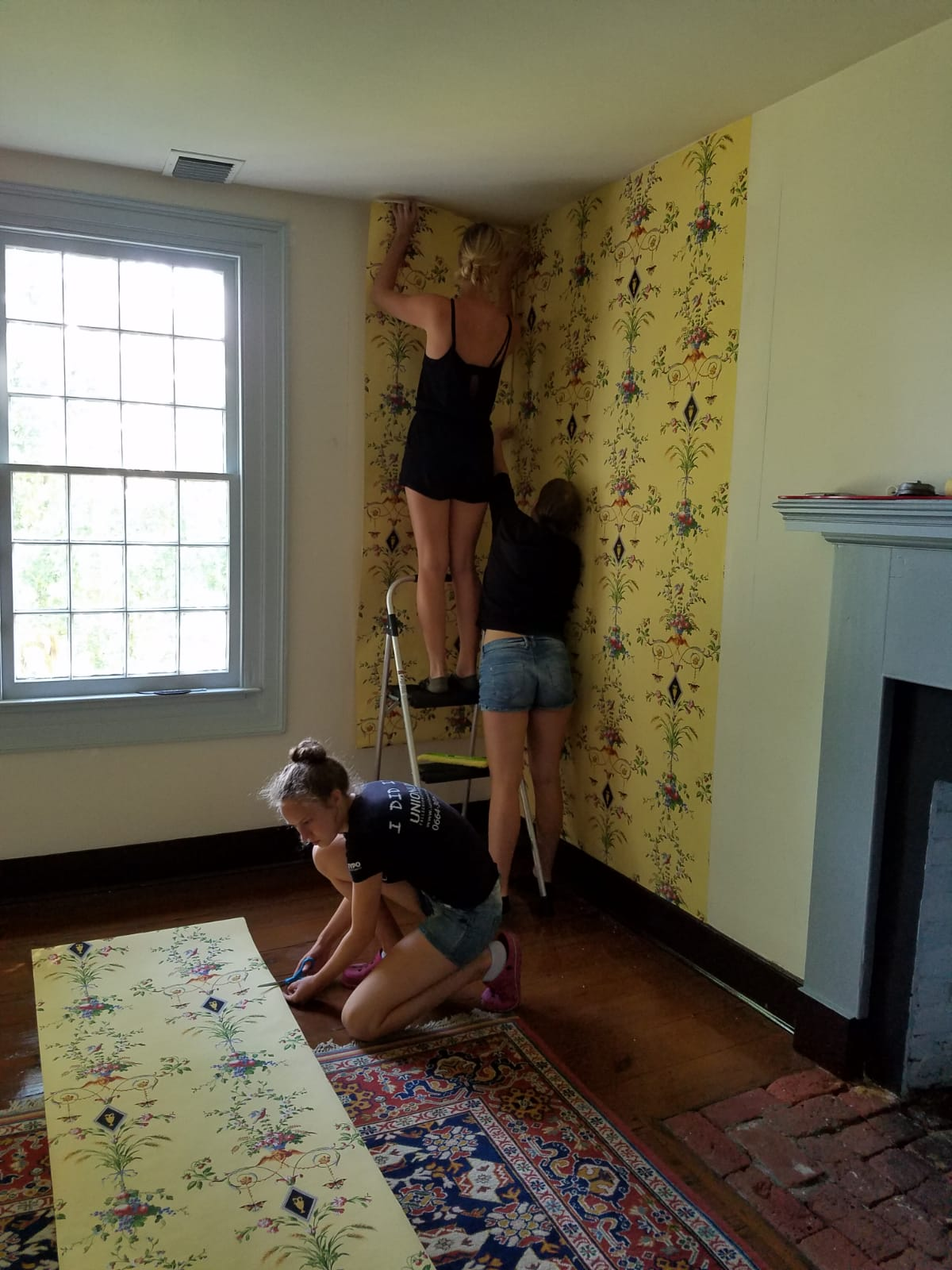 Tina and Lisa are hanging a piece into a corner (tricky!) while Monika is preparing to cut another section.