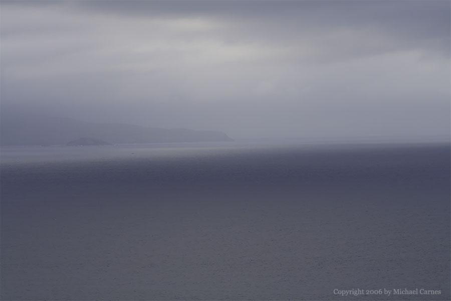The island of Molokini, viewed through fog on Maui
