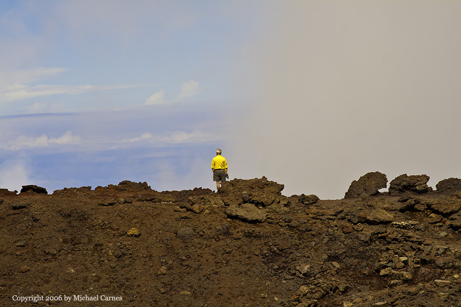 A man stands at the summit of Haleakala Volcano on Maui