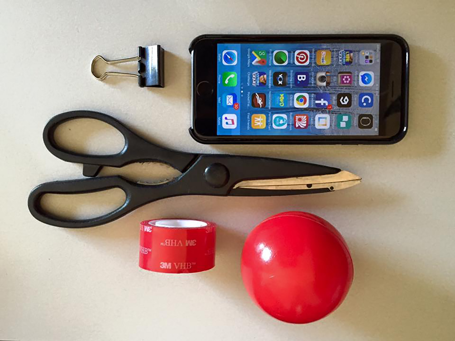 1. Gather Materials:  - Plastic ball - Double adhesive tape - Double clip (medium size) - Scissor - Smart Phone