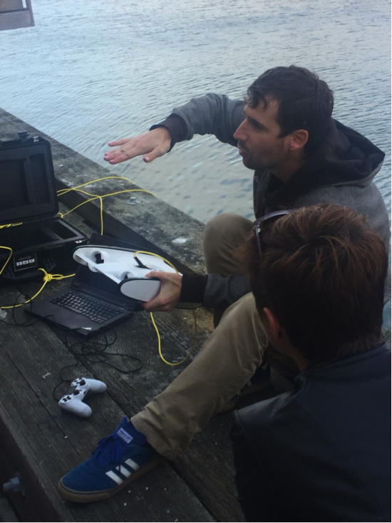 Eric Stackpole of OpenROV with their latest design, the Trident, in San Francisco March 2017. Note the game controller and the laptop, which displays tele-robotic views of what lies beneath the pier.   © Jennie Rose (used with permission)