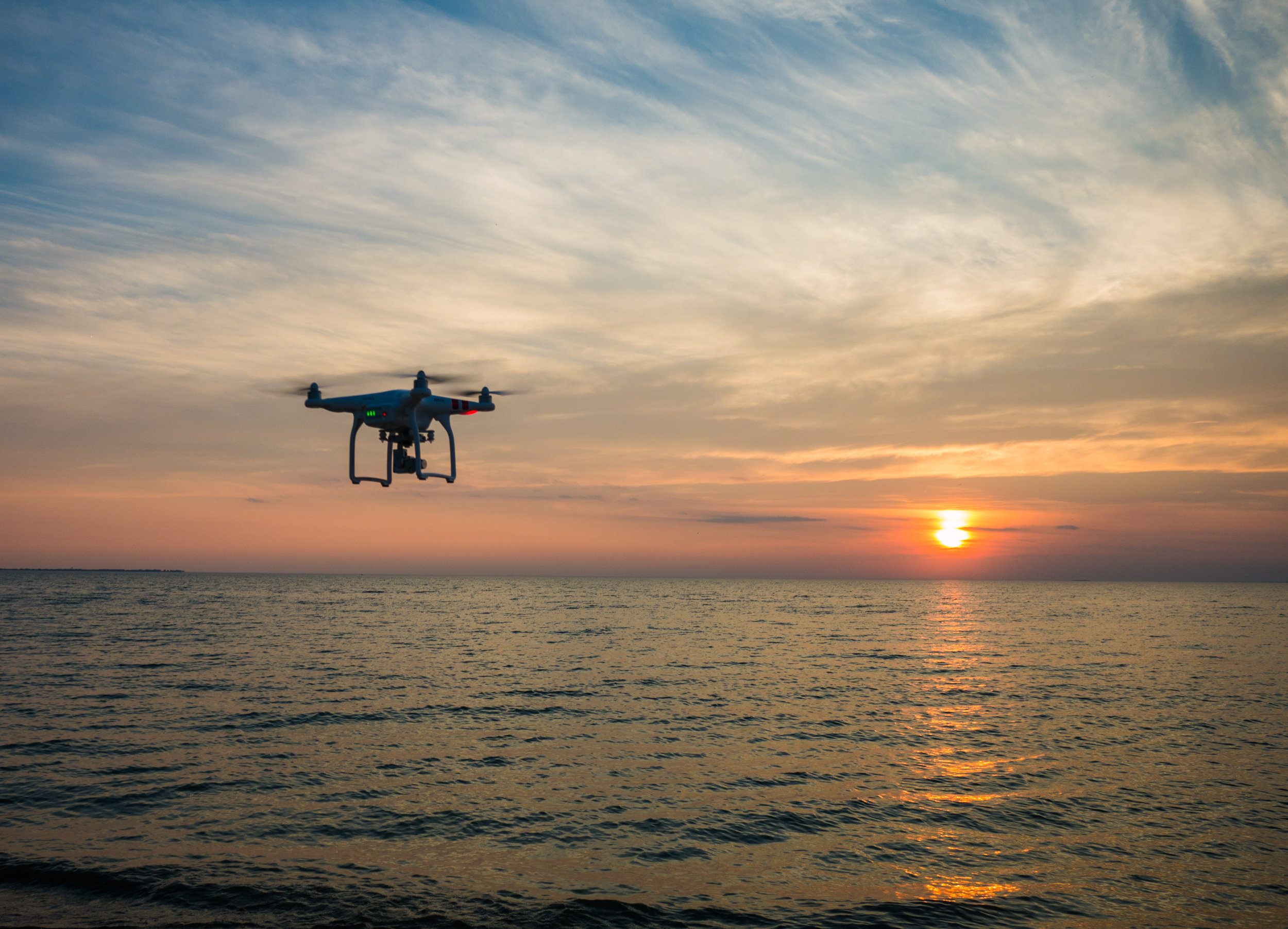 A drone flies toward a setting sun .  Aaron Burden/Unsplash  (CC0 1.0)