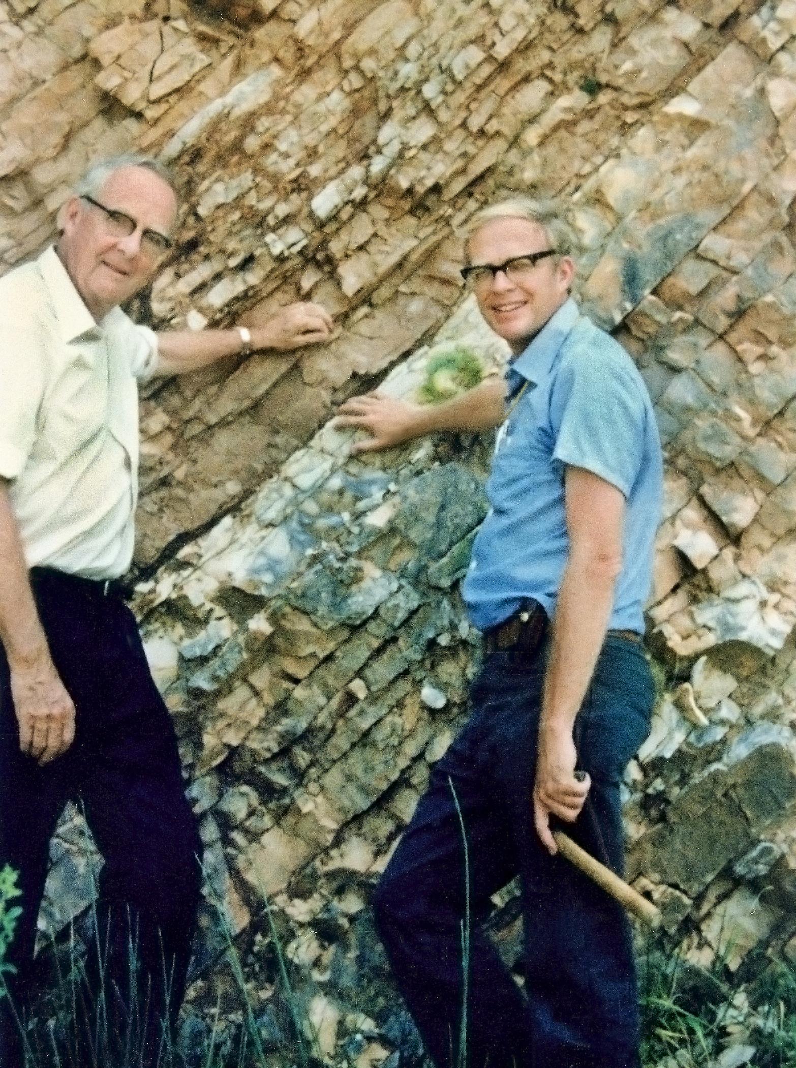 Physicist Luis Alvarez and his son, geologist Walter Alvarez, pose next to the Cretaceous-Tertiary boundary at Gubbio, Italy .  Lawrence Berkeley Laboratory/Wikimedia Commons  (public domain)