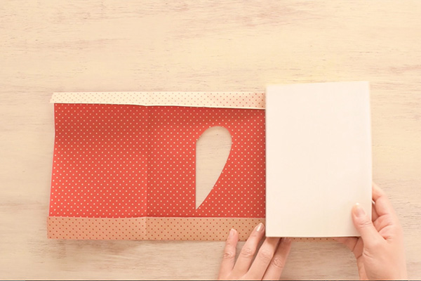 Step 9: Fold back the creases and wrap the paper around the book.