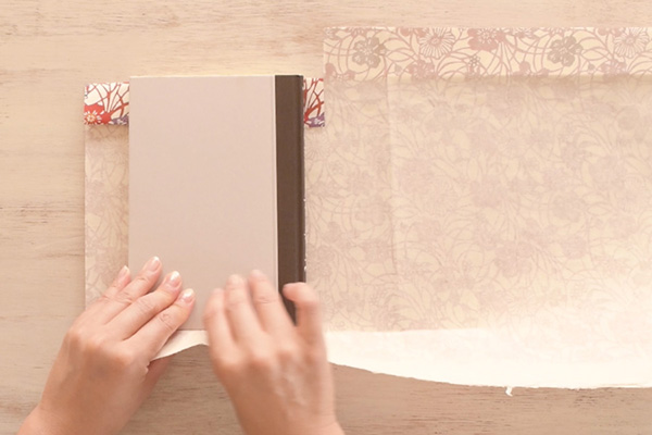 Step 7: Repeat the same steps on the other side. Mark to crease the paper at the height of the book.