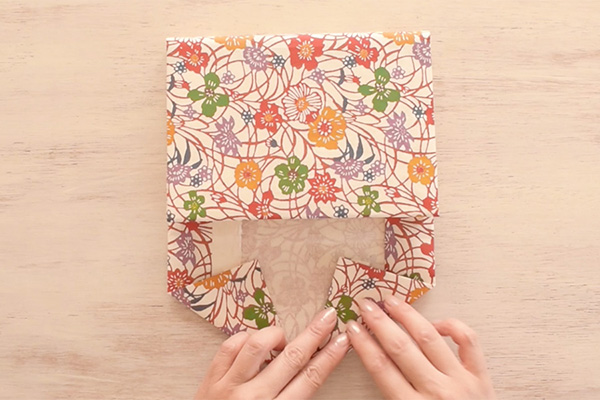 Step 15: Continue to fold the sides in triangles to create an envelope flap.