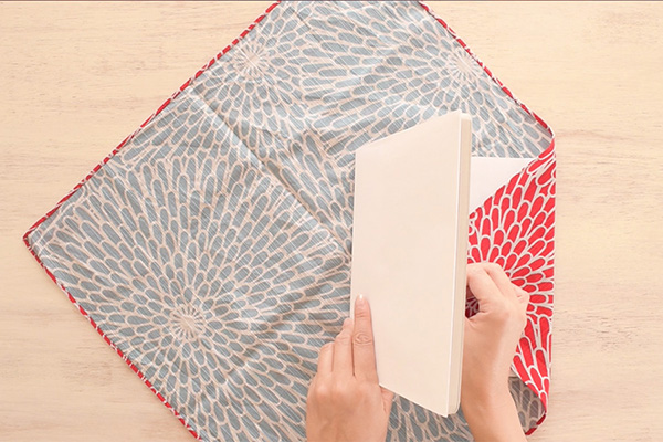 Step 2: Stand the book at the center, wrap the right side of Furoshiki around the cover of the book.
