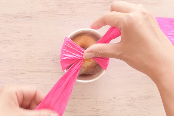 Step 7: Wrap the paper ribbon around the cup vertically, then cross at the top.