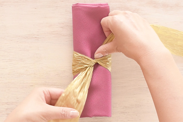 Step 2: Cross at the center to tighten the ribbon. The short end should still be on the right side.