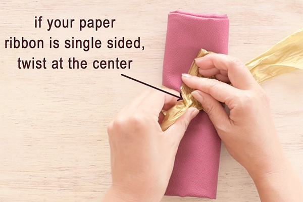 Step 4: Twist at the center if your paper ribbon is single sided, to show the front side ribbon. Skip this step if you're using double sided ribbon.