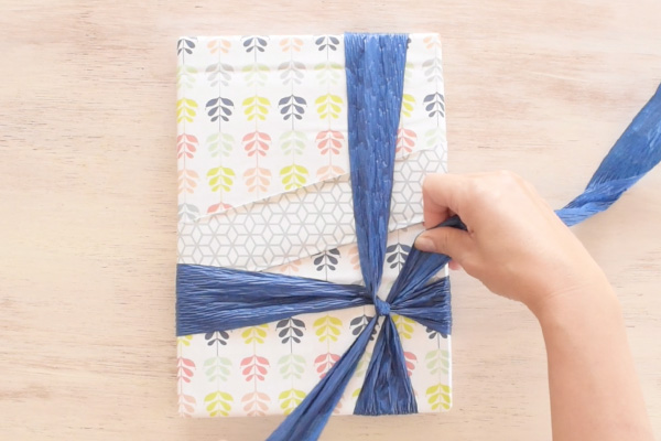 Step 9: Wrap the paper ribbon around the package and cross at the bottom right position.