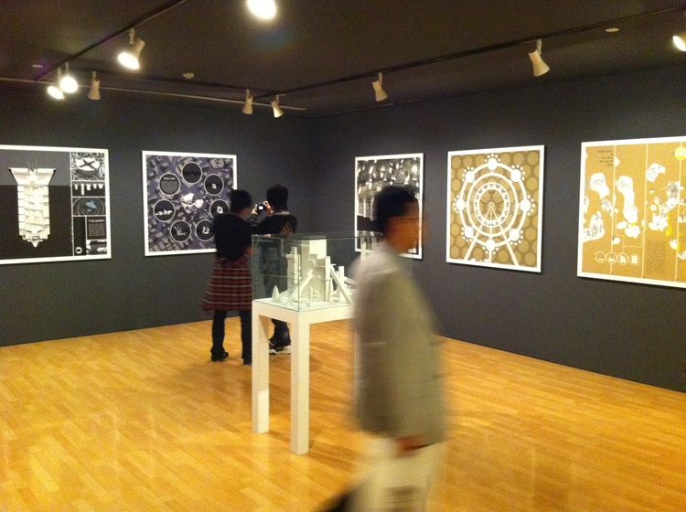 """Installation view of """"The 8th Shanghai Biennale 2010"""", Shanghai Art Museum, 2010:ON TABLE: Michael Lee,  The World Exposition , 2009-10, paper board and glue, various sizes on 1:1000 scale; ON WALLS: Michael Lee,  Spiral Supermart ,  Shishitv Tower ,  era-SERS ,  EcoFlyer  and  Island Square , from the series """"Second-Hand City"""", 2010,photo by Michael Lee."""