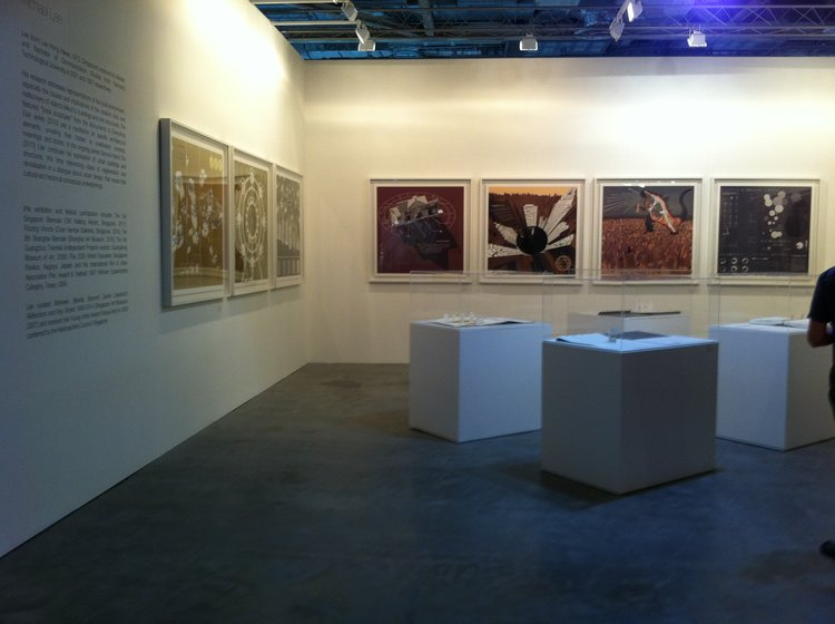 """Installation view at """"Art Stage Singapore"""", Marina Bay Sands, 2011:ON WALLS: Michael Lee, Island Square ,  EcoFlyer ,  era-SERS ,  Halved Hay House ,  Cropped City , all 2010, Karmastica Republic ,  No Unturned Stone,  both   2011, from the series """"Second-Hand City""""; ON PLINTHS: Michael Lee, selection from the series """"Monuments to Everything Else"""", presented by Chan Hampe Galleries, Singapore, photo by Michael Lee."""