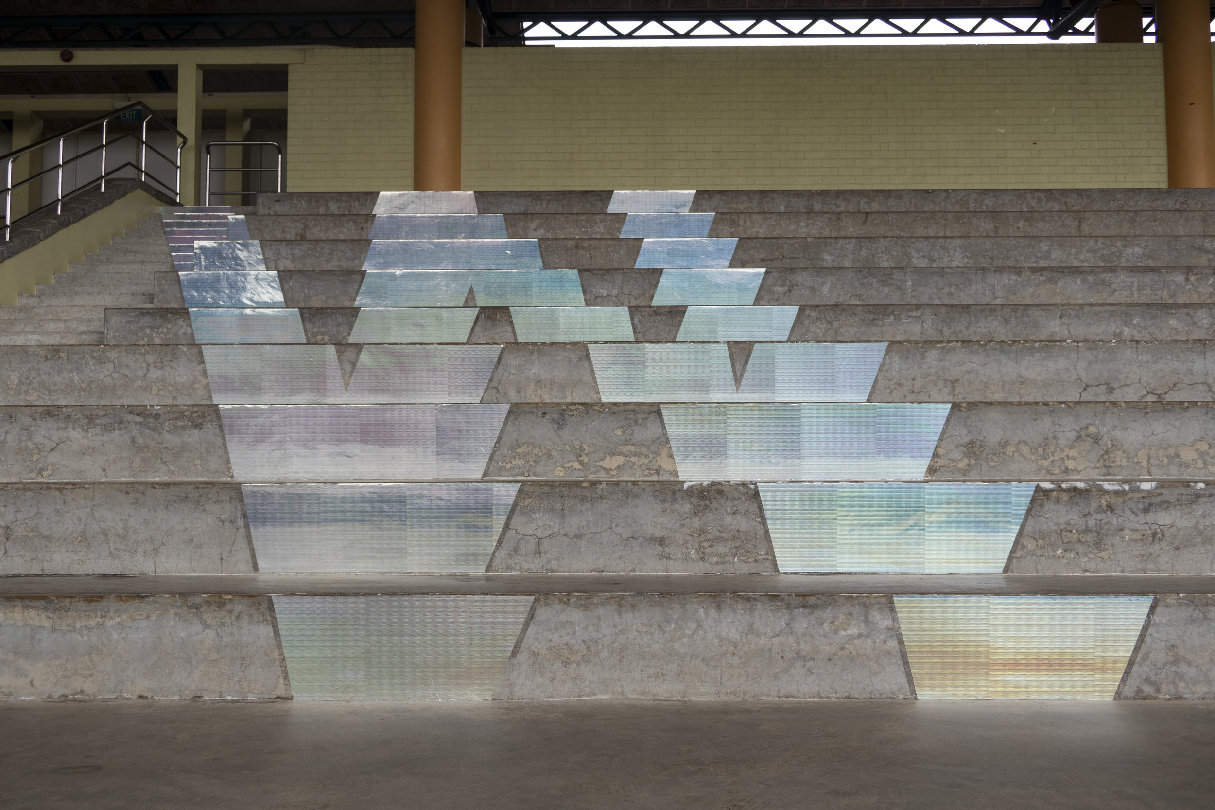 "Michael Lee,  How are things  (detail), 2018, holographic stickers on risers on Woodlands Stadium grandstand, Singapore, part of the public art exhibition, ""Placing Home: Woodlands"", curated by Wang Ruo Bing for Arts in Your Neighbourhood, 2018. Photo by Ken Cheong."
