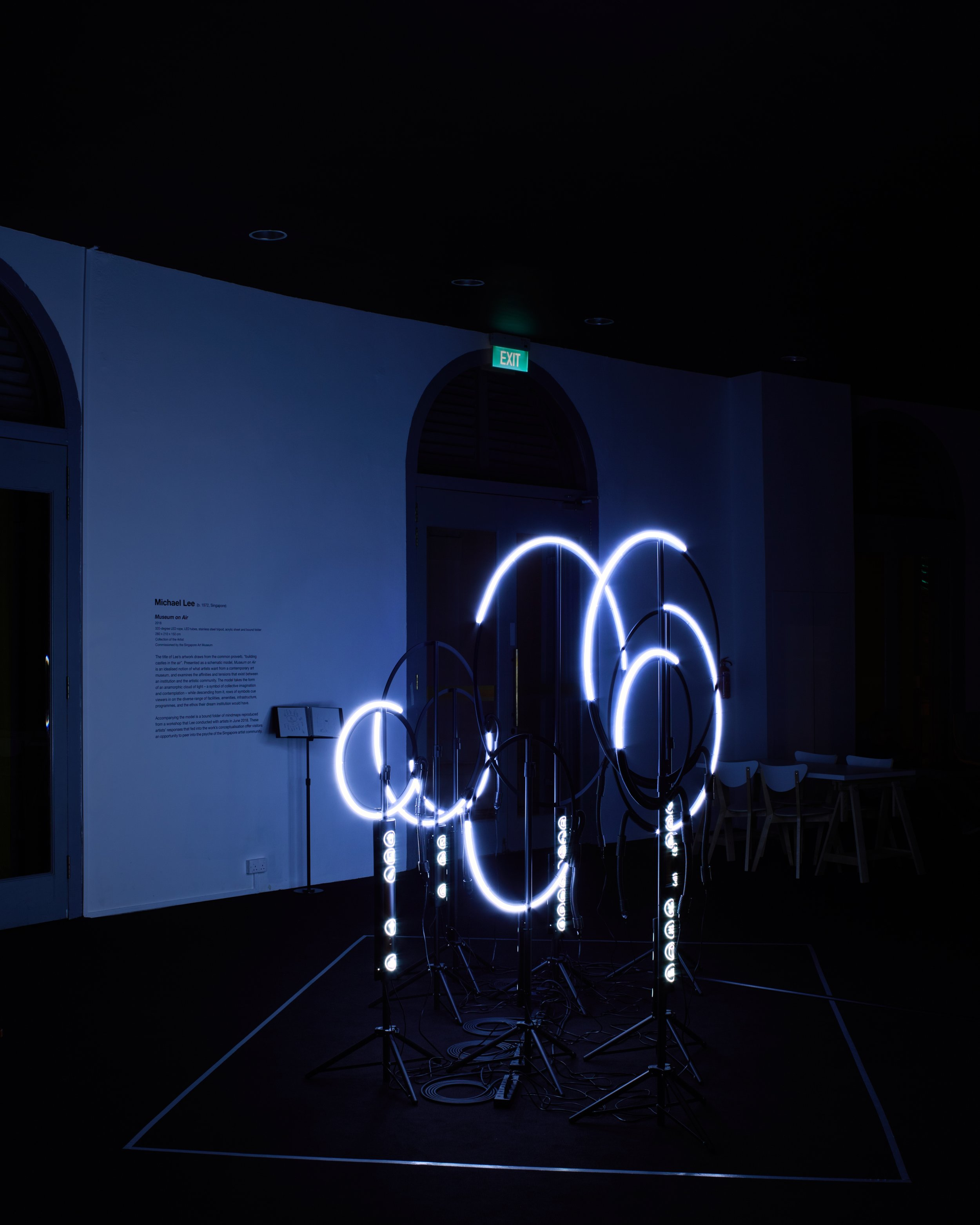 "Michael Lee,  Museum on Art  (oblique view), 2018, 320-degree LED ropes, vinyl stickers on LED lamps, matt enamel spraypaint on perspex sheets, steel tripods and cable ties, dimensions variable, part of the exhibition ""Installation in Progress"" curated by John Tung at Curve, Singapore Art Museum. Photo by Tan Hai Han."