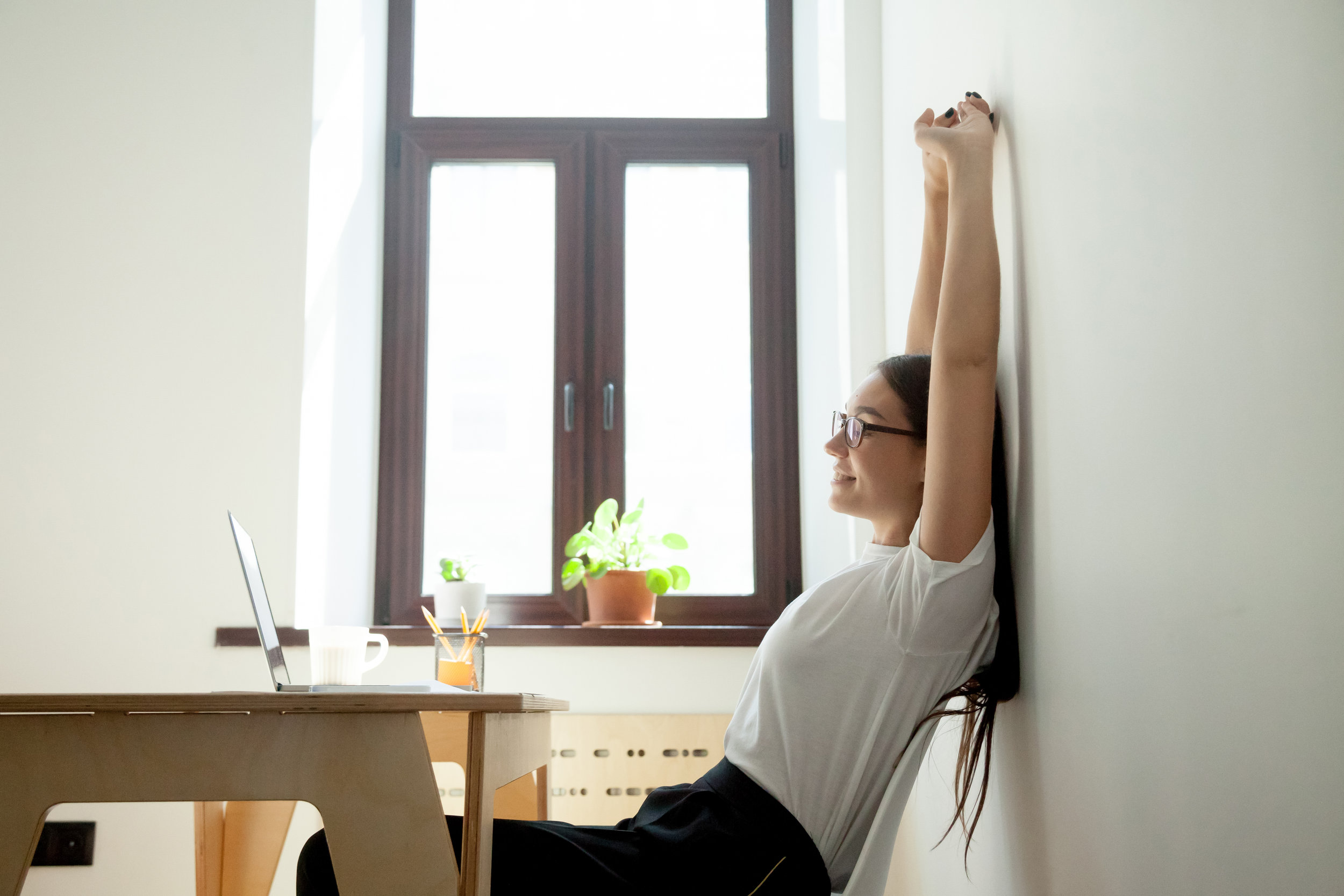 Attractive-young-businesswoman-relaxing,-stretching-at-desk-in-home-office-889206762_5349x3566.jpeg